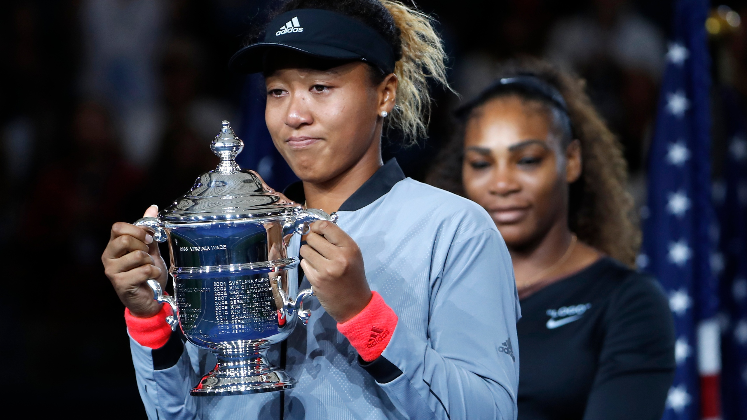 Naomi Osaka, of Japan, holds the trophy after defeating Serena Williams, rear, in the women's final of the U.S. Open tennis tournament in New York on Sept. 8, 2018. (Adam Hunger/Associated Press)
