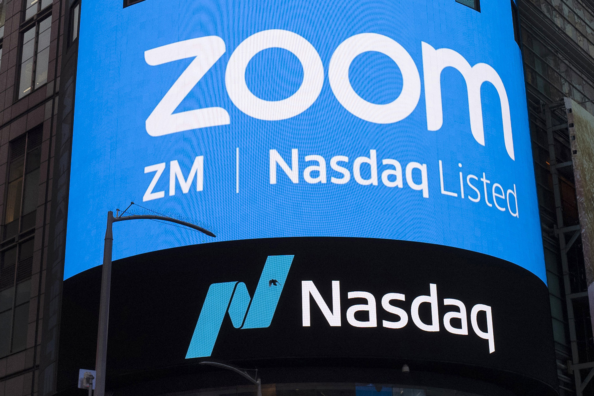 This April 18, 2019, file photo shows a sign for Zoom Video Communications ahead of their Nasdaq IPO in New York. (AP Photo/Mark Lennihan, File)