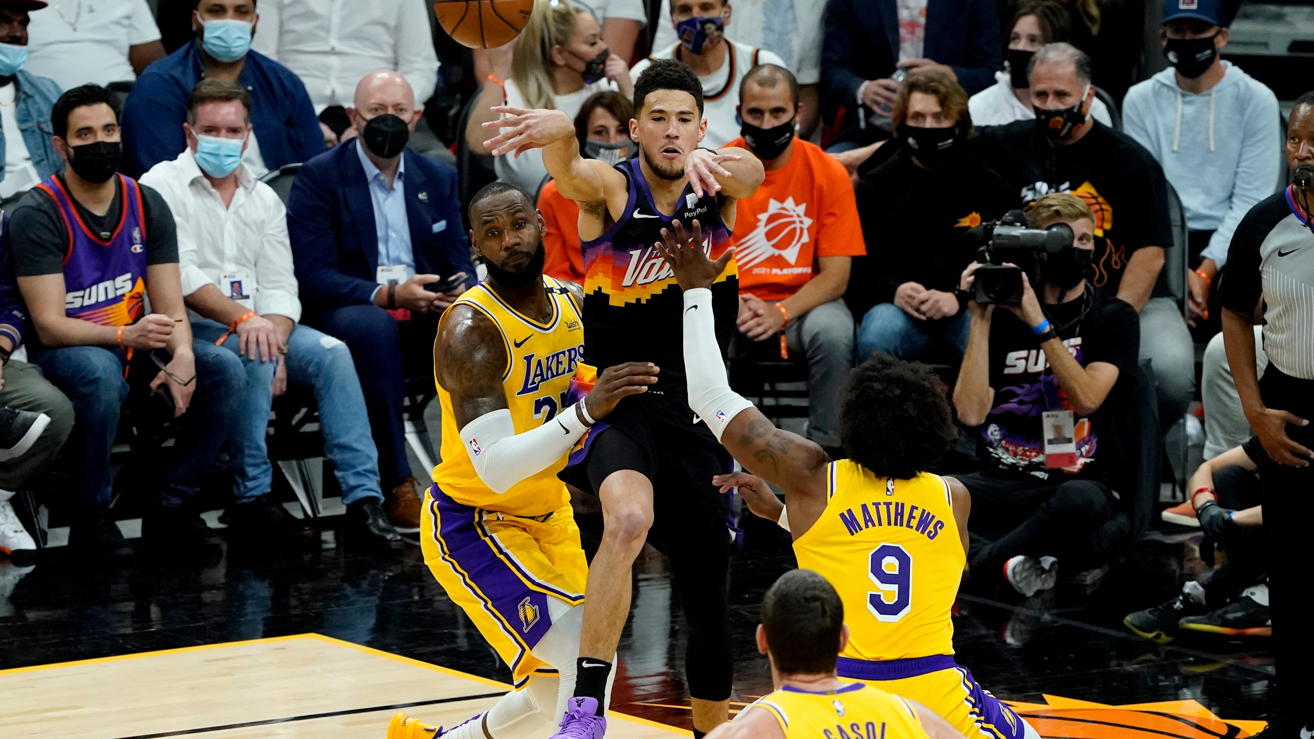 Phoenix Suns guard Devin Booker passes over Los Angeles Lakers forward LeBron James, left, and guard Wesley Matthews (9) during the first half of Game 5 of an NBA basketball first-round playoff series on June 1, 2021, in Phoenix. (AP Photo/Matt York)