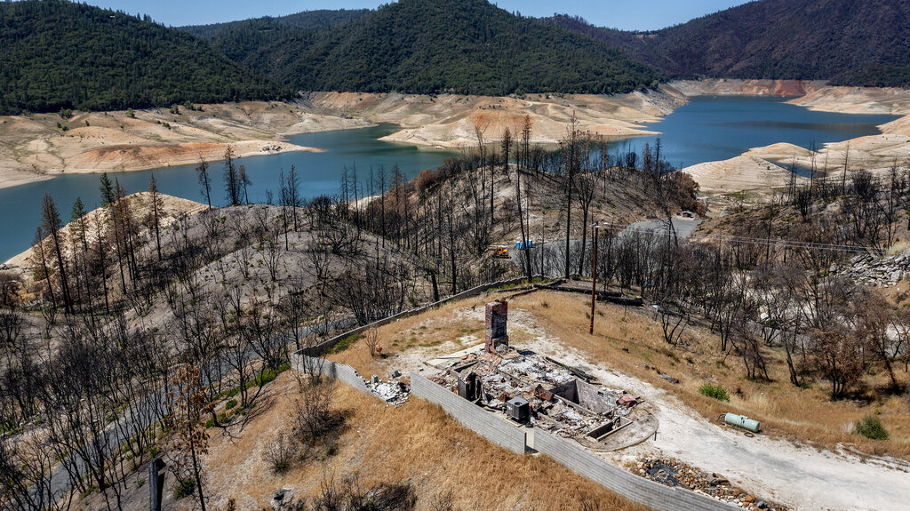 A home destroyed in the 2020 North Complex Fire sits above Lake Oroville on Sunday, May 23, 2021, in Oroville, Calif. (AP Photo/Noah Berger)