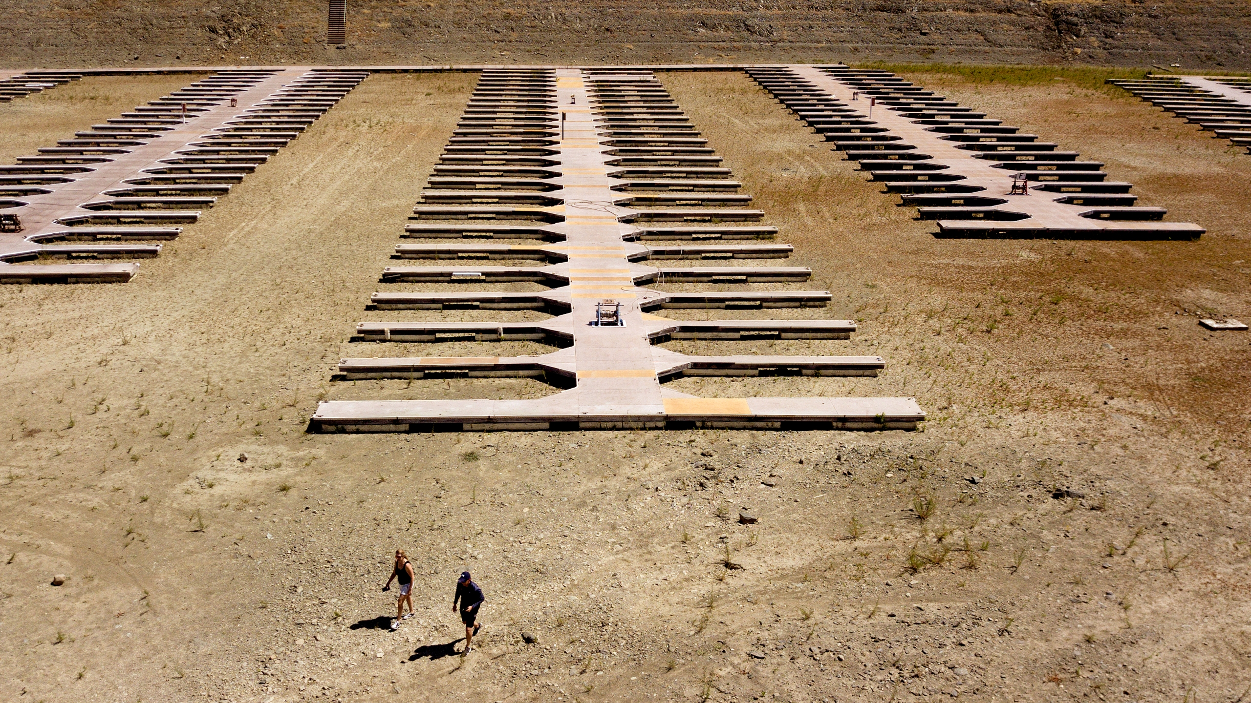 People walk near boat docks as they sit on dry land at the Browns Ravine Cove area of drought-stricken Folsom Lake. (AP Photo/Josh Edelson)