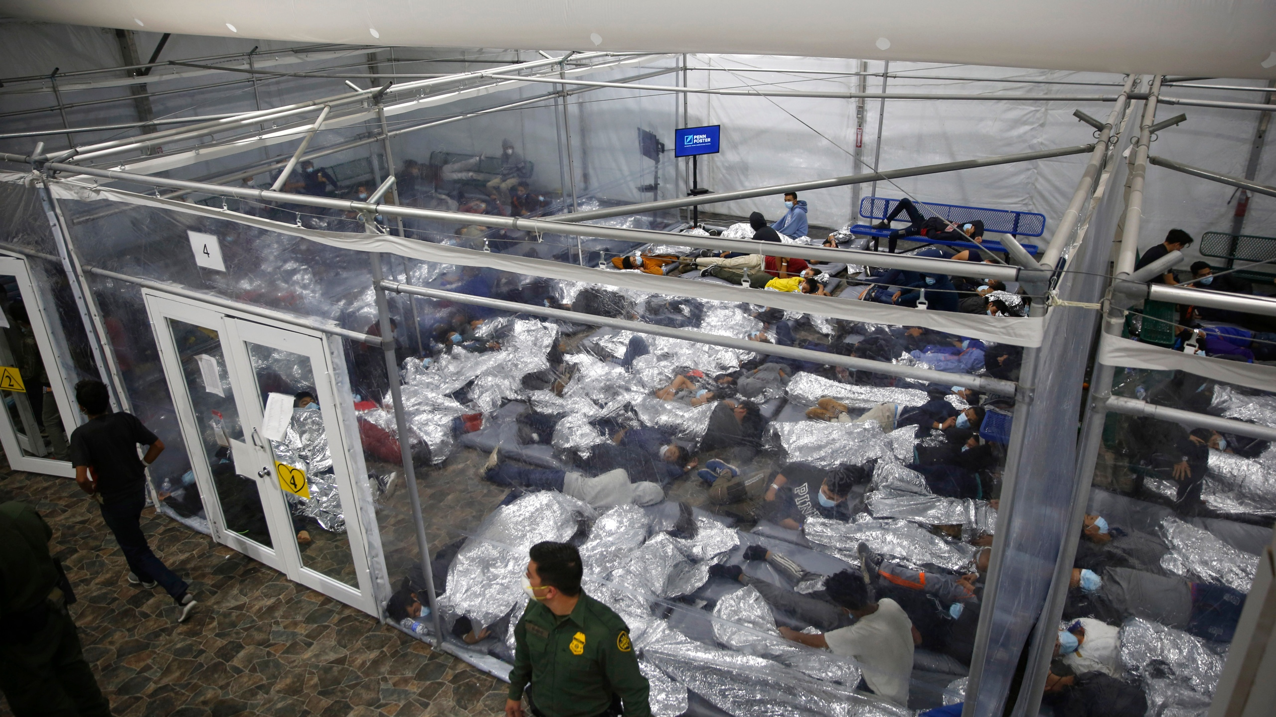 """In this March 30, 2021, file photo, minors lie inside a pod at the Donna Department of Homeland Security holding facility, in Donna, Texas. A move by Texas Gov. Greg Abbott to shutter dozens of shelters housing about 4,000 migrant children is threatening to disrupt a national program offering care for minors who cross the U.S.-Mexico border. The U.S. Department of Health and Human Services said Wednesday, June 2 2021, that it didn't intend to close any facilities but that it was """"assessing"""" the Republican governor's late Tuesday disaster declaration. (AP Photo/Dario Lopez-Mills, Pool, File)"""