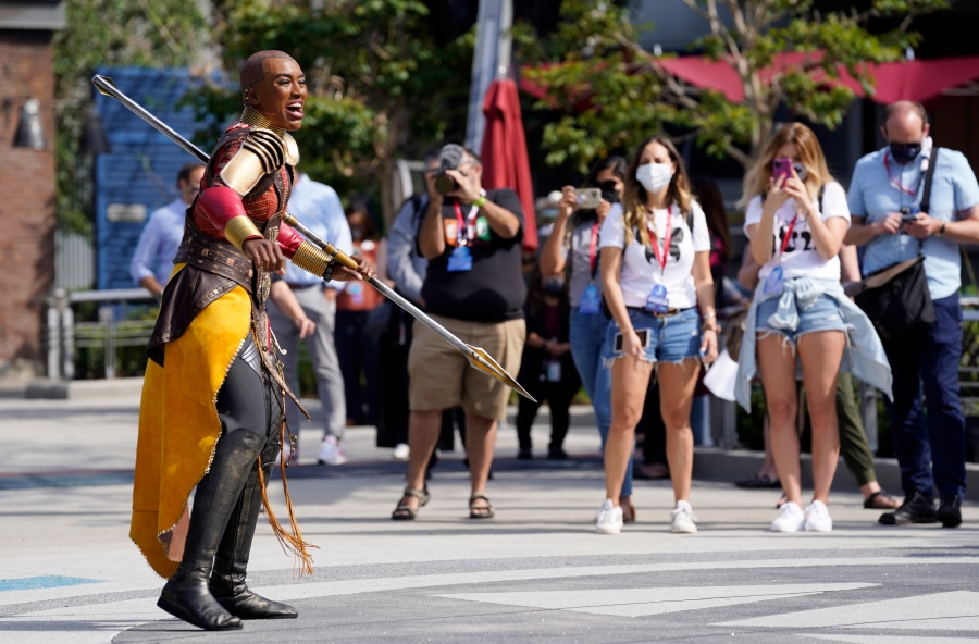 """Guests look on as a character from the film """"Black Panther"""" performs during """"The Warriors of Wakanda: The Disciplines of the Dora Milaje"""" show at the Avengers Campus media preview at Disney's California Adventure Park on June 2, 2021, in Anaheim, Calif. (AP Photo/Chris Pizzello)"""