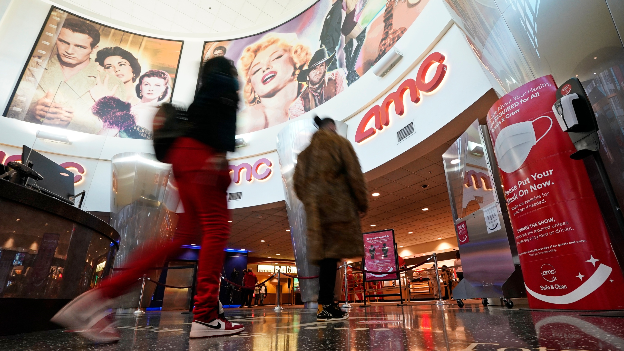 In this March 15, 2021, file photo movie patrons arrive to see a film at the AMC 16 theater in Burbank, Calif. AMC is looking to sell up to 11.5 million of its shares, as the movie theater operator looks to capitalize on its meme stock popularity. The announcement in a regulatory filing on Thursday, June 3 comes just two days after the company said it was raising $230.5 million through an 8.5 million share sale. (AP Photo/Mark J. Terrill, File)