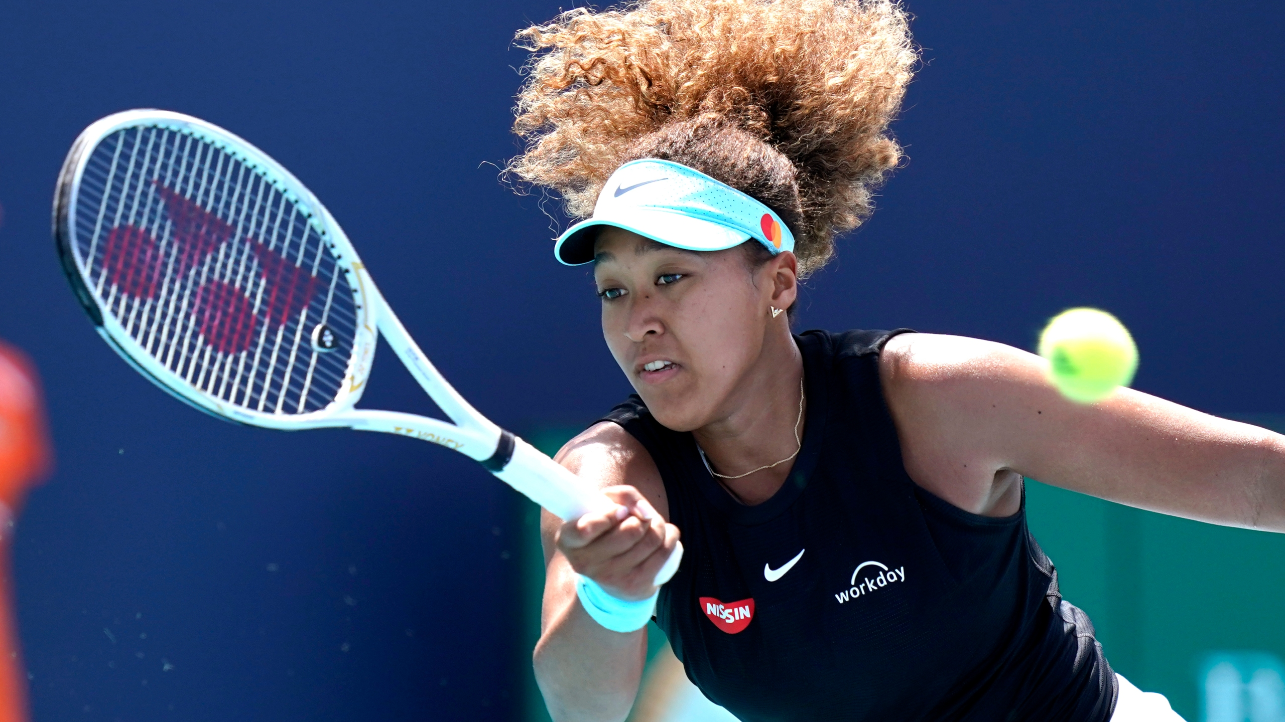 In this March 31, 2021 file photo, Naomi Osaka, of Japan, returns to Maria Sakkari, of Greece, during the quarterfinals of the Miami Open tennis tournament in Miami Gardens, Fla. Sponsors of Osaka are sticking by the her after she withdrew from the French Open, citing mental health issues relating to the press conferences required for players. Osaka, a four-time Grand Slam champion, said Monday, May 31, she was withdrawing from the French Open for mental health issues. (AP Photo/Lynne Sladky, File)