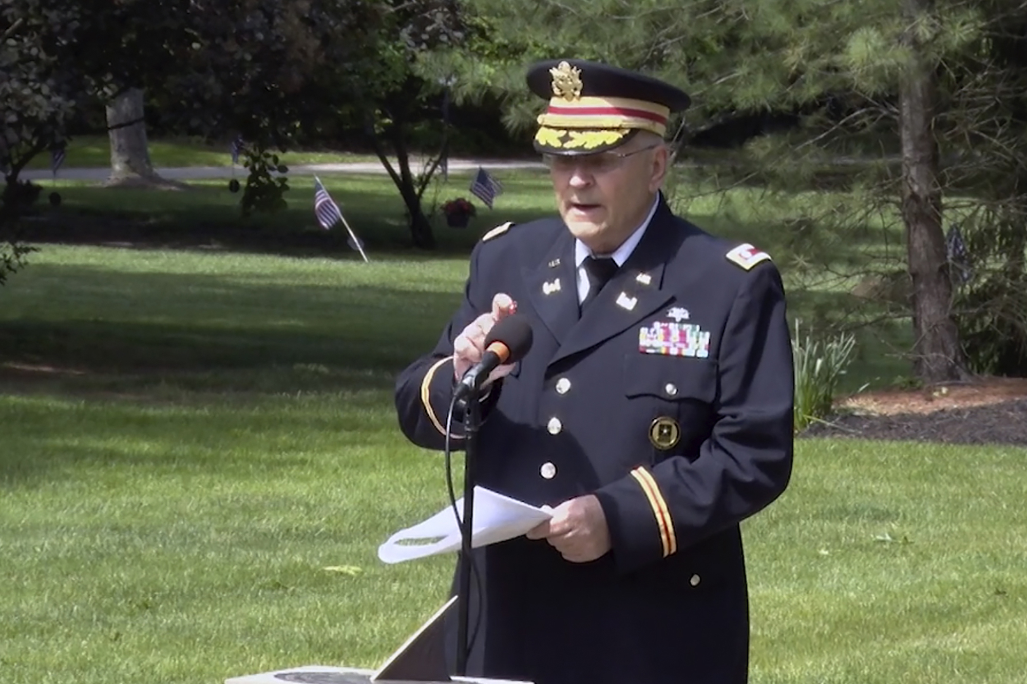 In this frame grab from video provided by Hudson Community Television, retired Army Lt. Col. Barnard Kemter taps the microphone after organizers turned off the audio during his speech at a Memorial Day ceremony, Monday, May 31, 2021, in Hudson, Ohio. Organizers of the ceremony turned off Kemter's microphone when he began talking about how freed Black slaves had honored fallen soldiers soon after the Civil War. (Hudson Community Television via AP)