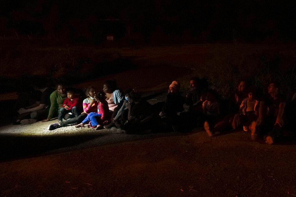 Migrants mainly from Honduras and Nicaragua sit in line after turning themselves in upon crossing the U.S.-Mexico border Monday, May 17, 2021, in La Joya, Texas. (AP Photo/Gregory Bull, file)