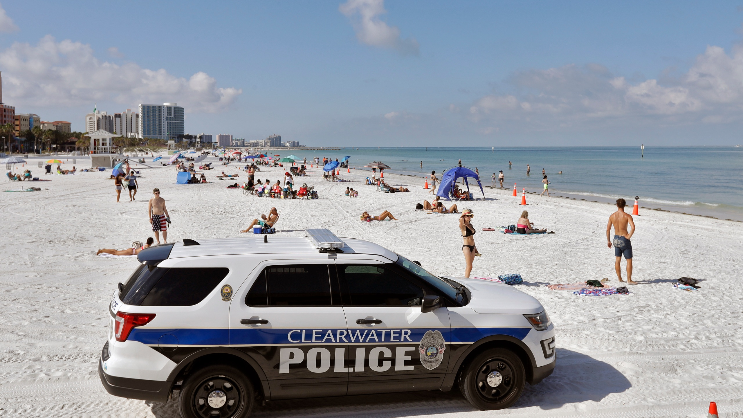 In this Monday, May 4, 2020 file photo, police officers patrol the area after Clearwater Beach officially reopened to the public in Clearwater Beach, Fla. (AP Photo/Chris O'Meara, File)