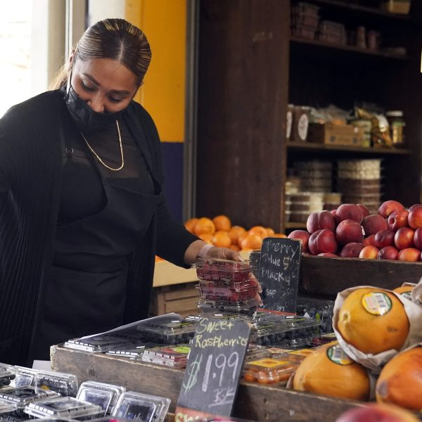 A worker wears a mask while setting up a fruit display amid the COVID-19 pandemic at The Farmers' Market in Los Angeles on May 20, 2021. (Marcio Jose Sanchez / Associated Press)