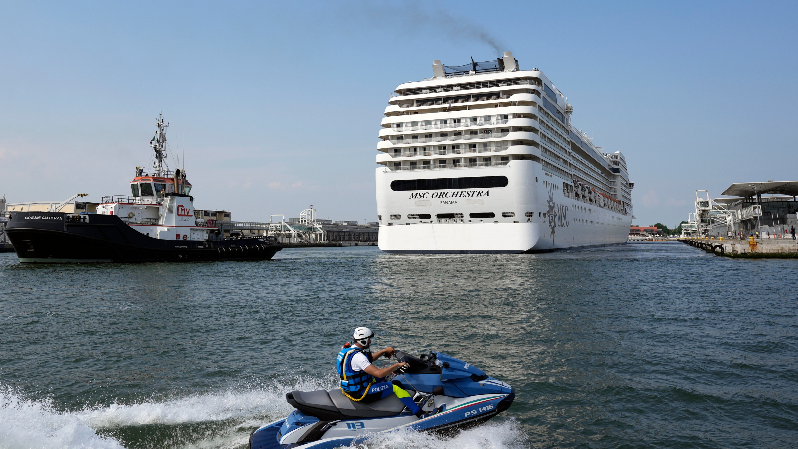 The the 92,409-ton, 16-deck MSC Orchestra cruise ship exits the lagoon as it leaves Venice, Italy, Saturday, June 5, 2021. (AP Photo/Antonio Calanni)