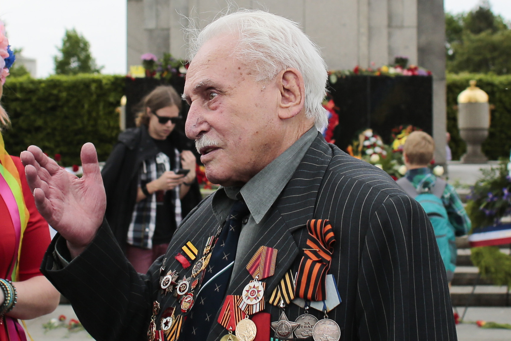 In this Friday, May 8, 2015 file photo, Soviet war veteran David Dushman, 92, center, speaks to people holding Ukrainian flags as he attends a wreath laying ceremony at the Russian War Memorial in the Tiergarten district of Berlin, Germany. Dushman, the last surviving Allied soldier involved in the liberation of Auschwitz, has died. The Jewish Community of Munich and Upper Bavaria said Sunday, June 6, 2021 that Dushman had died a day earlier in a Munich hospital at the age of 98. As young Red Army soldier, Dushman flattened the forbidding fence around the notorious Nazi death camp with his tank on Jan. 27, 1945. (AP Photo/Markus Schreiber, File)