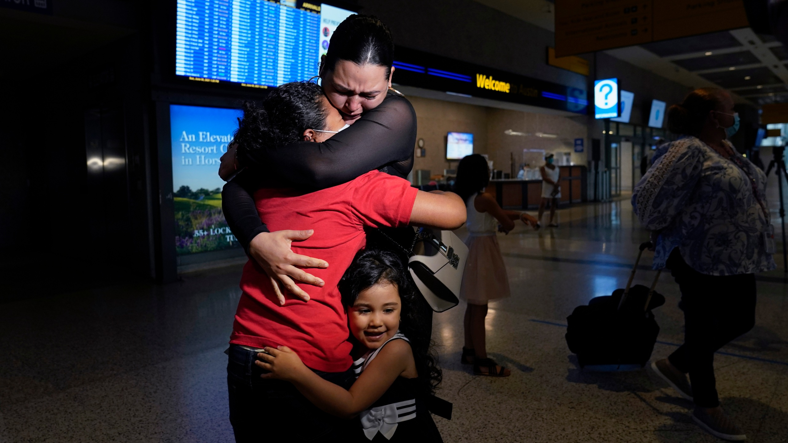 Emely, left, is reunited with her mother, Glenda Valdez and sister, Zuri, at Austin-Bergstrom International Airport, Sunday, June 6, 2021, in Austin, Texas. It had been six years since Valdez said goodbye to her daughter Emely in Honduras. Then, last month, she caught a glimpse of a televised Associated Press photo of a little girl in a red hoodie and knew that Emely had made the trip alone into the United States. On Sunday, the child was returned to her mother's custody. (AP Photo/Eric Gay)