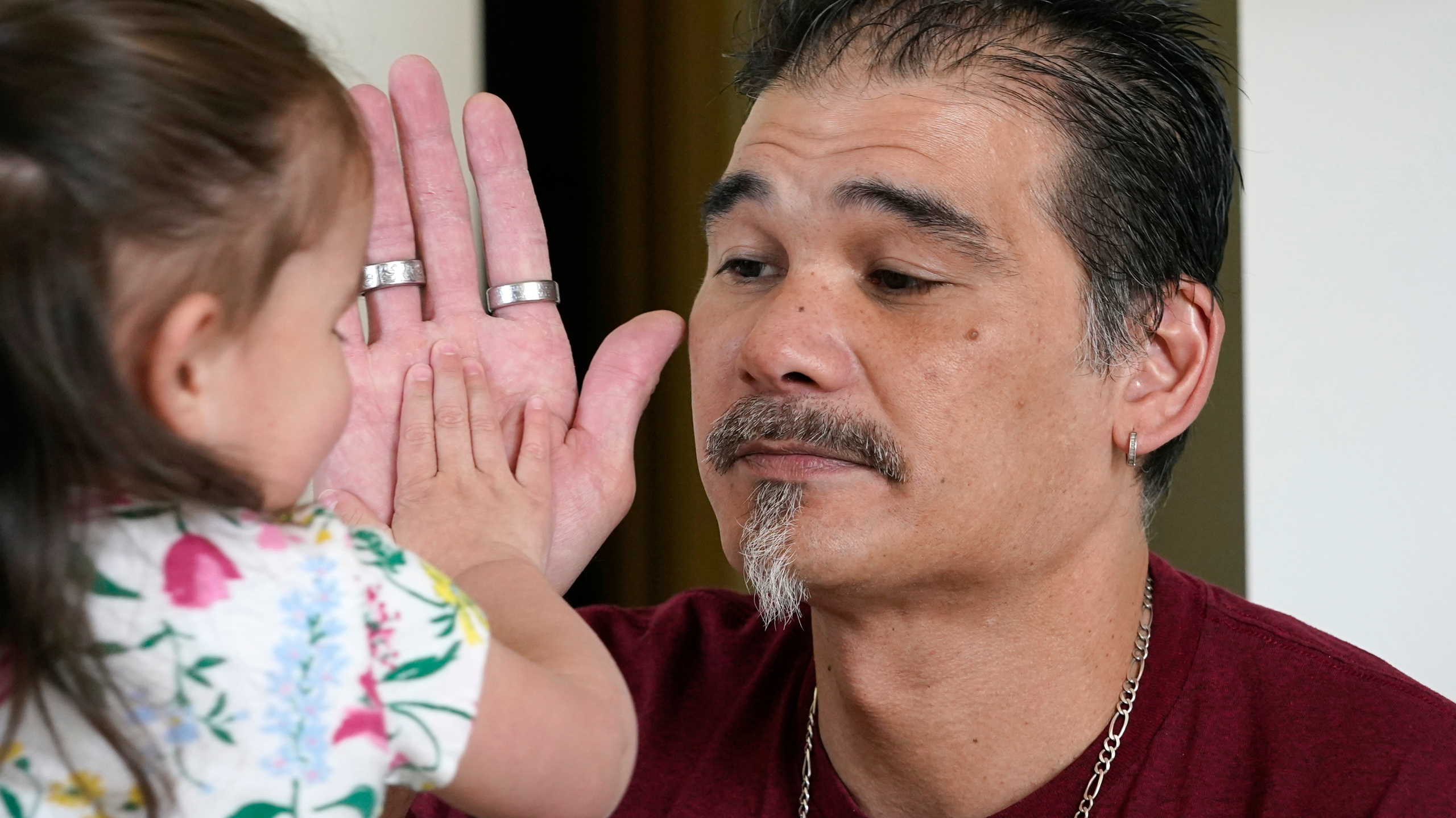 Leroy Pascubillo touches hands with his daughter, who was born addicted to heroin and placed with a foster family at birth, May 10, 2021, in Seattle. Pascubillo, who had used drugs for the better part of four decades, was in a court-ordered in-patient drug rehab program when the pandemic first hit. (AP Photo/Elaine Thompson)