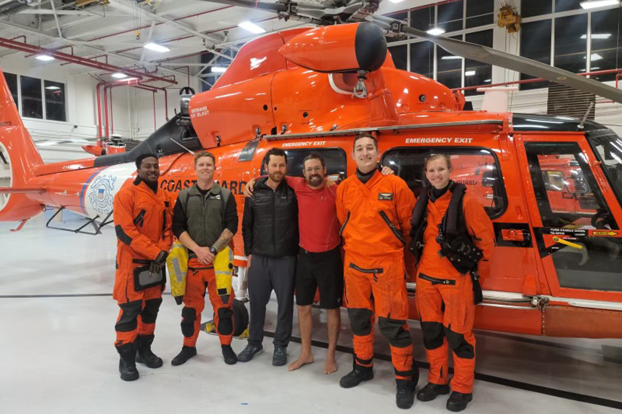 In this photo provided by the U.S. Coast Guard, kayaker Cyril Derreumaux, in shorts, poses with the Coast Guard helicopter crew that rescued him off the California coast in San Francisco on June 5, 2021.