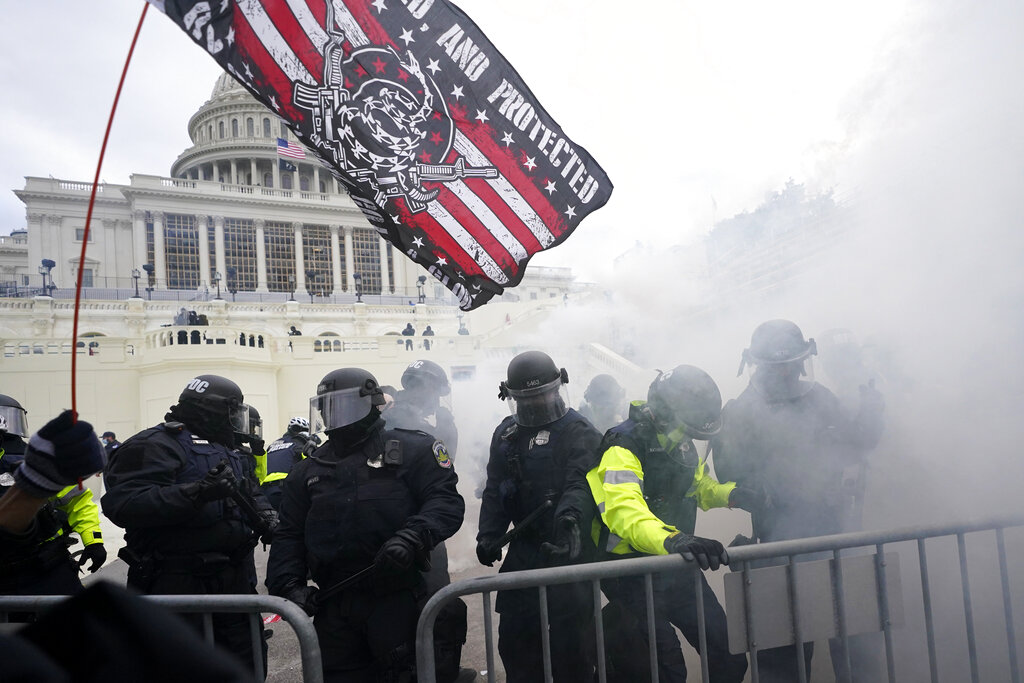 In this Jan. 6, 2021, U.S. Capitol Police officers hold off rioters loyal to President Donald Trump at the Capitol in Washington. (AP Photo/Julio Cortez, File)