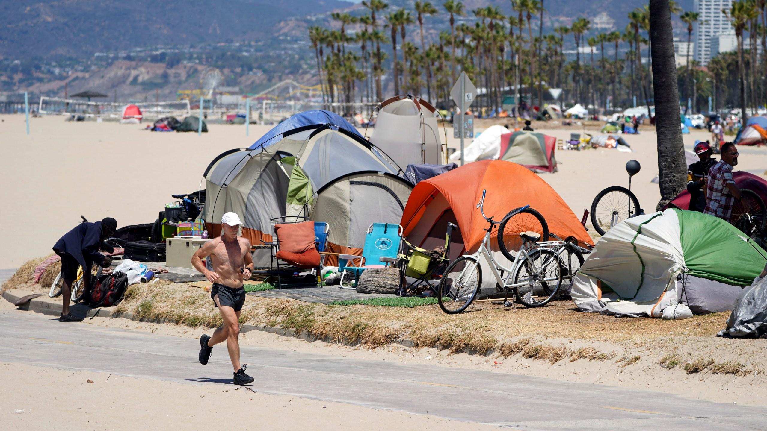 A jogger walks past a homeless encampment Tuesday, June 8, 2021, in the Venice Beach section of Los Angeles. (AP Photo/Marcio Jose Sanchez)