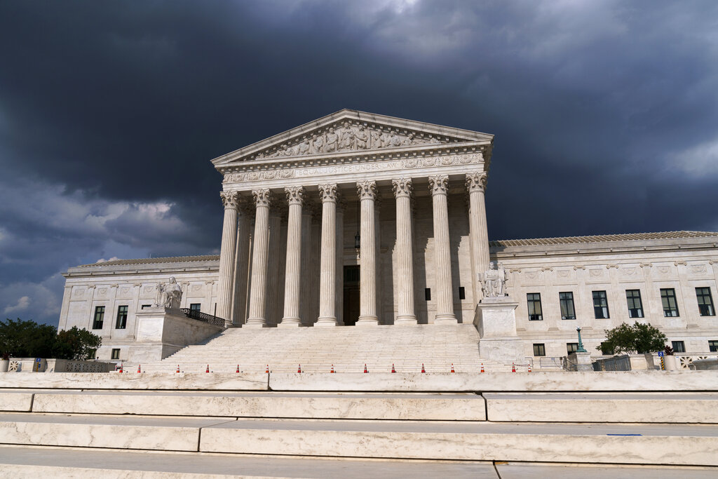 In this June 8, 2021 photo, with dark clouds overhead, the Supreme Court is seen in Washington. (AP Photo/J. Scott Applewhite)
