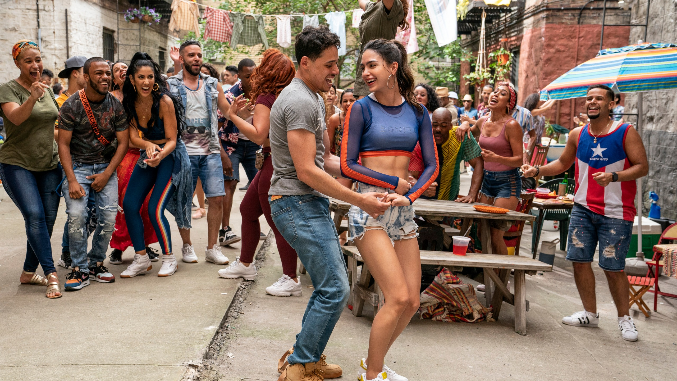 """This image released by Warner Bros. Picures shows Anthony Ramos, foreground left, and Melissa Barrera in a scene from """"In the Heights."""" (Macall Polay/Warner Bros. Entertainment via AP)"""