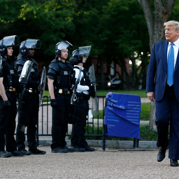 In this June 1, 2020 file photo, President Donald Trump walks past police in Lafayette Park after visiting outside St. John's Church across from the White House in Washington. (AP Photo/Patrick Semansky)