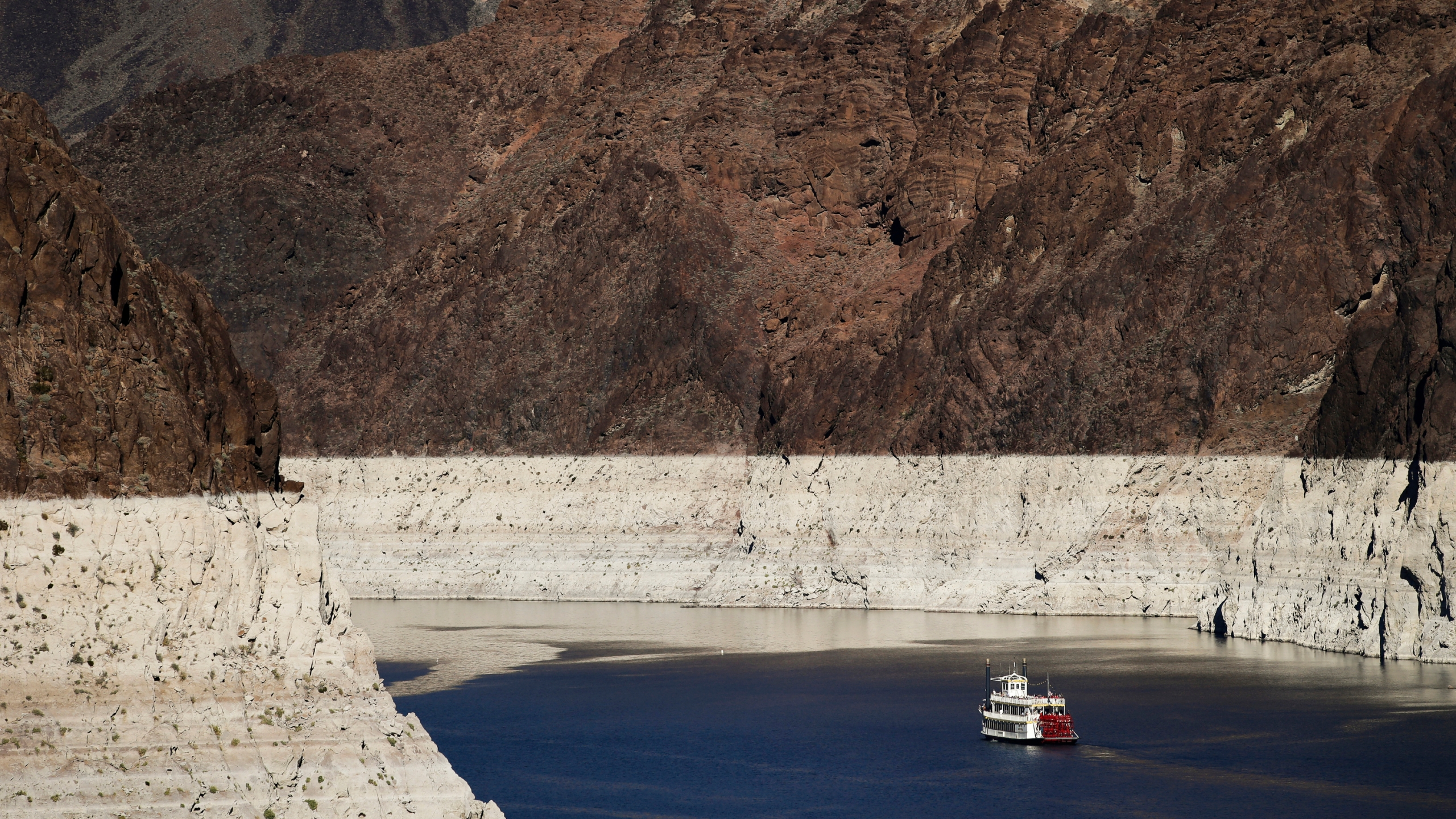 In this Oct. 14, 2015, file photo, a riverboat glides through Lake Mead on the Colorado River at Hoover Dam near Boulder City, Nev. The key reservoir on the Colorado River is expected to match its record low level on Thursday, June 10, 2021. The dropping surface elevation of Lake Mead along the Arizona-Nevada border is the another sign of the drought's grip on the region. (AP Photo/Jae C. Hong, File)