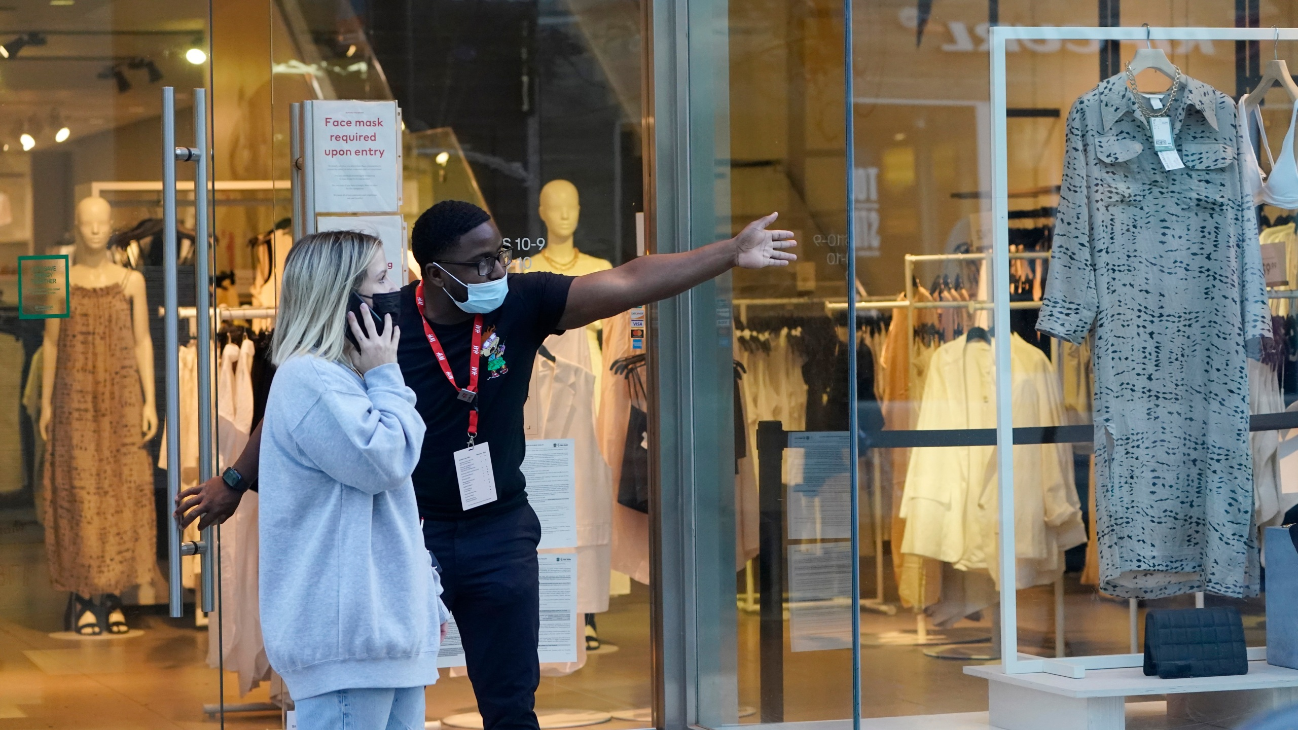A salesperson gives directions to a shopper amid the COVID-19 pandemic on The Promenade Wednesday, June 9, 2021, in Santa Monica, Calif. (AP Photo/Marcio Jose Sanchez)