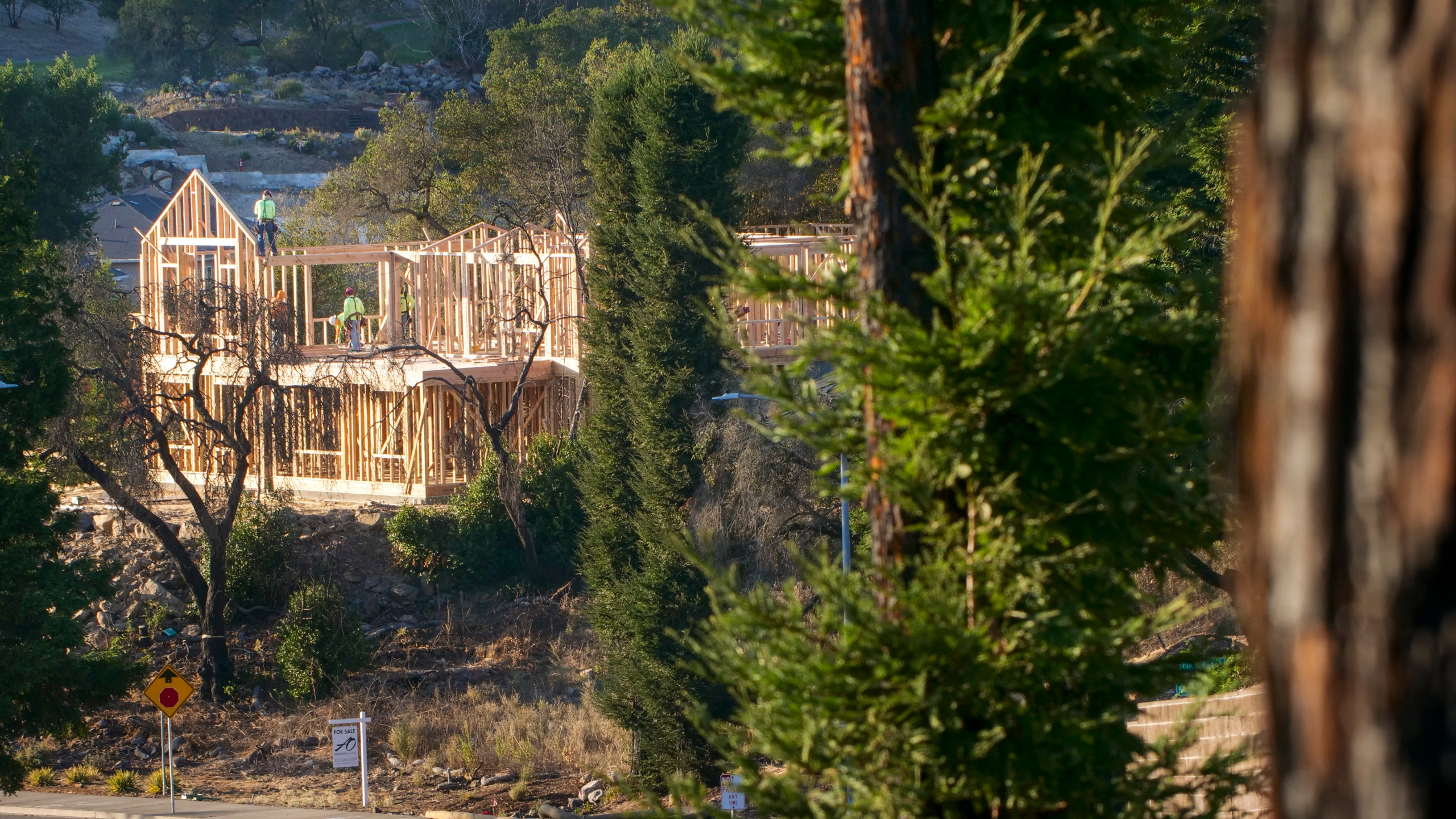 In this Tuesday, Nov. 5, 2019, file photo, builders work on a new home in Santa Rosa, Calif. California state and local officials are incentivizing rebuilding in areas destroyed by wildfires at a time when people should be redirected away from those areas if the state wants to reduce the economic and human impact of increasingly destructive wildfires, according to a report published Thursday, June 10, 2021. (AP Photo/Lacy Atkins, File)