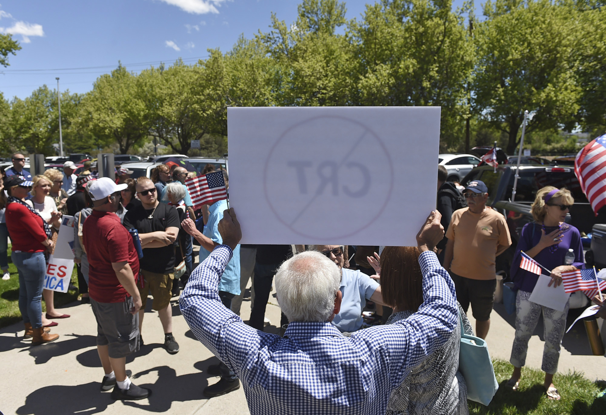 A man holds up a sign against Critical Race Theory during a protest outside a Washoe County School District board meeting on May 25, 2021, in Reno, Nev. Nevada school boards are becoming hotbeds of political polarization where parents are clashing over how to teach students about racism and its role in U.S. history. In Washoe County and Carson City, parents spoke Tuesday, June 8, 2021, against the concept of critical race theory being taught in schools, despite the fact that officials in both districts insist they have no plans to include it in lesson plans. (Andy Barron/Reno Gazette-Journal via AP)