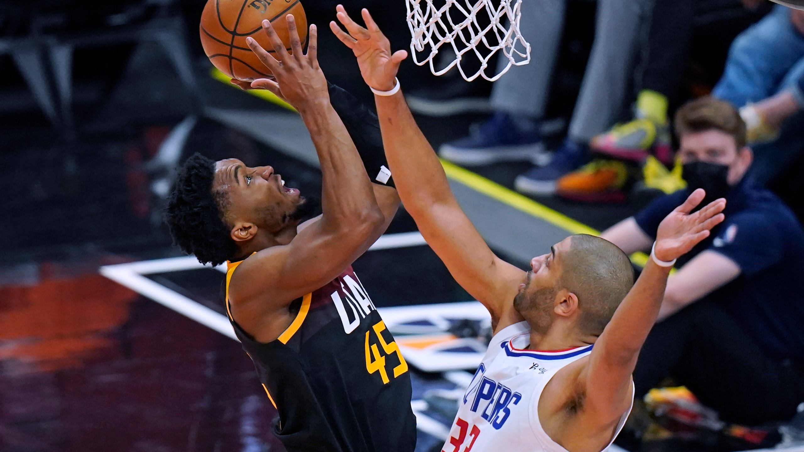 Los Angeles Clippers forward Nicolas Batum (33) defends as Utah Jazz guard Donovan Mitchell, left, goes to the basket during the first half of Game 2 of a second-round NBA basketball playoff series on June 10, 2021, in Salt Lake City. (Rick Bowmer / Associated Press)
