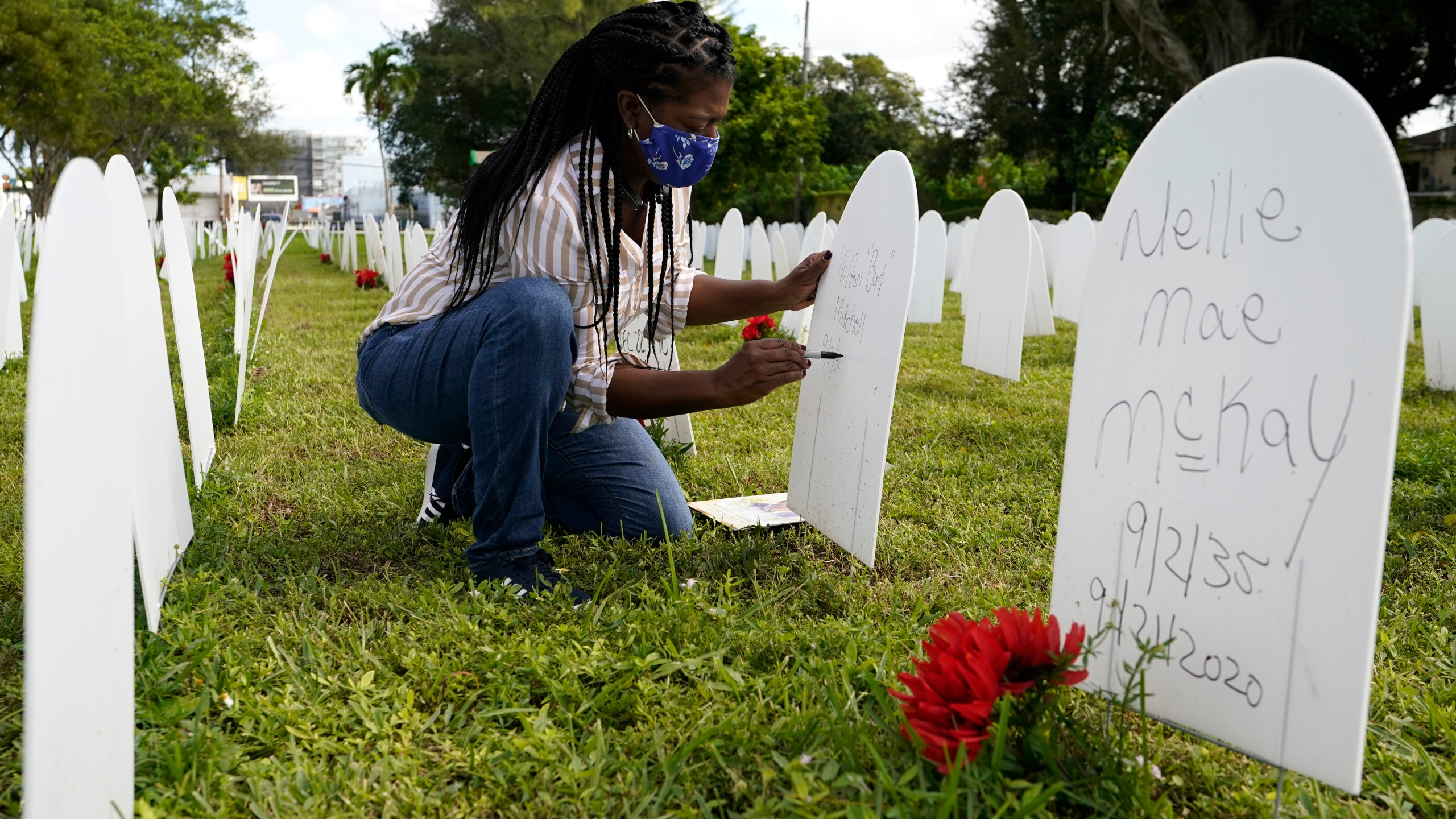 """In this Nov. 24, 2020, file photo, Joanna Moore writes a tribute to her cousin Wilton """"Bud"""" Mitchell who died of COVID-19 at a symbolic cemetery created to remember and honor lives lost to COVID-19, in the Liberty City neighborhood of Miami. The U.S. death toll from COVID-19 has topped 600,000, even as the vaccination drive has drastically slashed daily cases and deaths and allowed the country to emerge from the gloom. (AP Photo/Lynne Sladky, File)"""