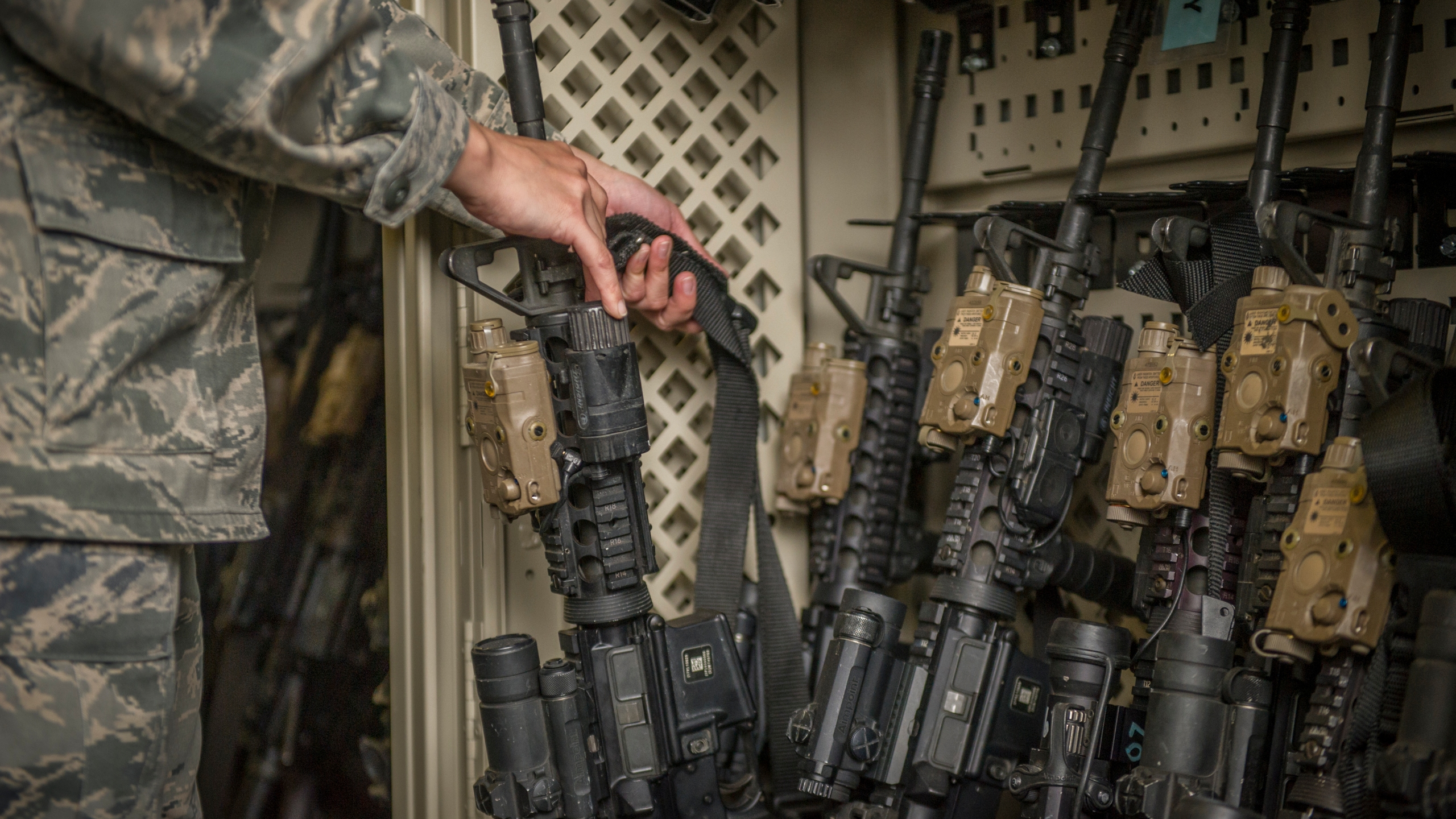 In this April 2, 2015, photo made available by the U.S. Air Force, a senior airman from the 49th Security Forces Squadron in charge of the armory, returns an M4 carbine to a rack at Holloman Air Force Base, N.M. (Airman 1st Class Aaron Montoya/U.S. Air Force via AP)