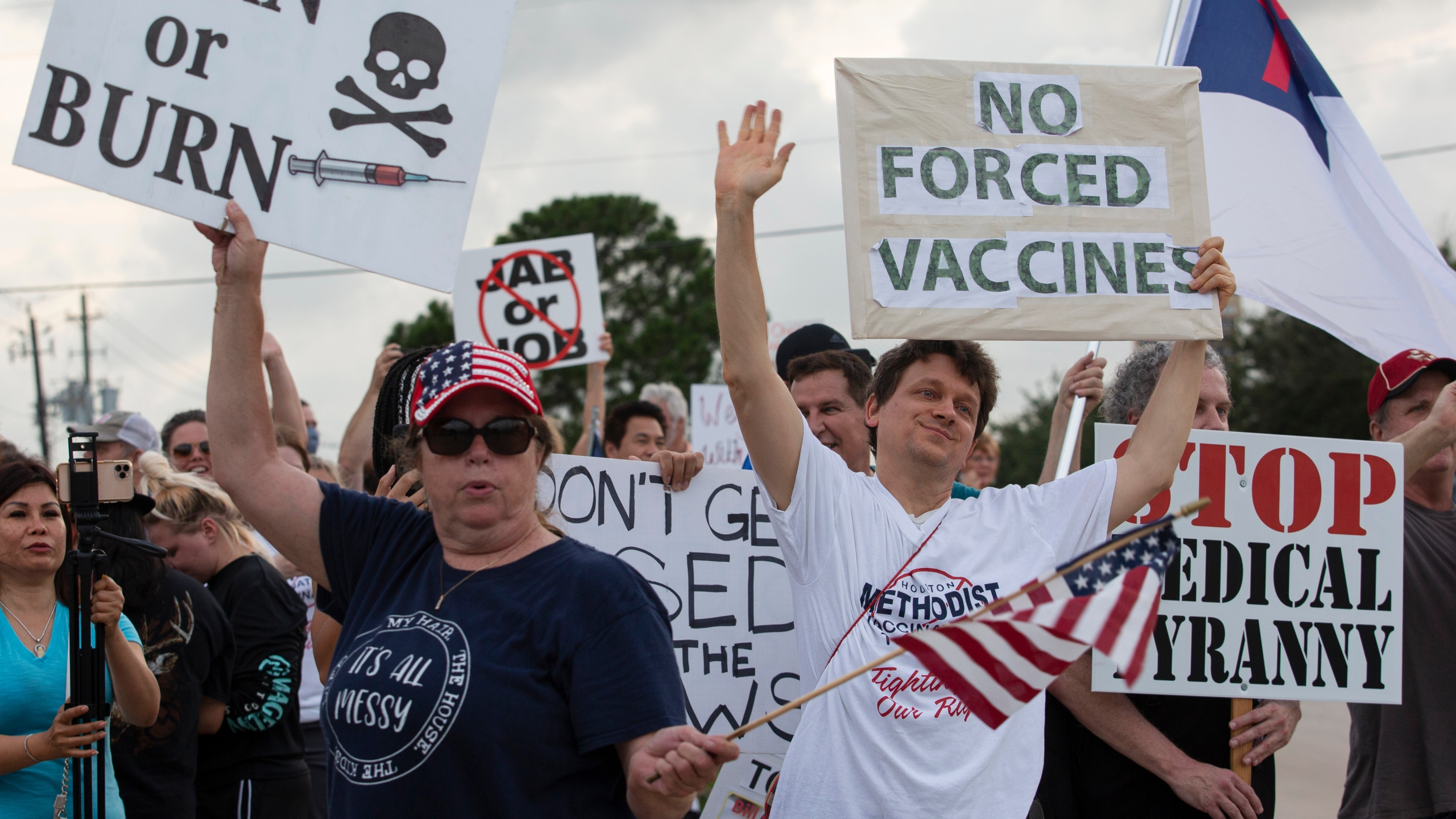 In this June 7, 2021, file photo, demonstrators at Houston Methodist Baytown Hospital in Baytown, Texas, wave at cars that honk at them to support their protest against a policy that says hospital employees must get vaccinated against COVID-19 or lose their jobs. (Yi-Chin Lee/Houston Chronicle via AP)