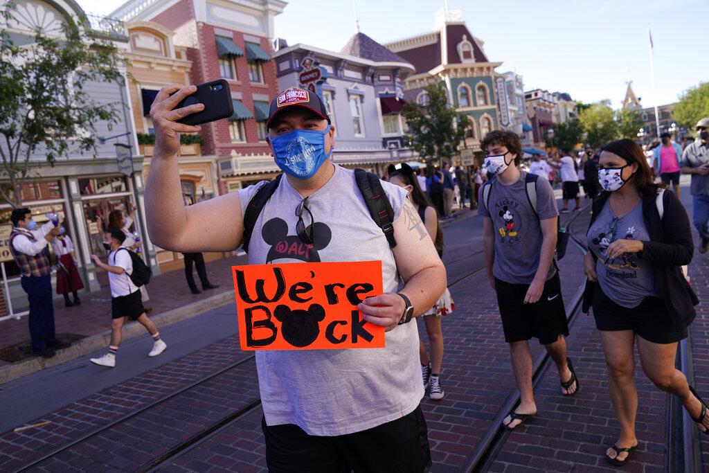In this Friday, April 30, 2021, file photo, visitors walk down Main Street USA at Disneyland in Anaheim, Calif. (AP Photo/Jae Hong, File)