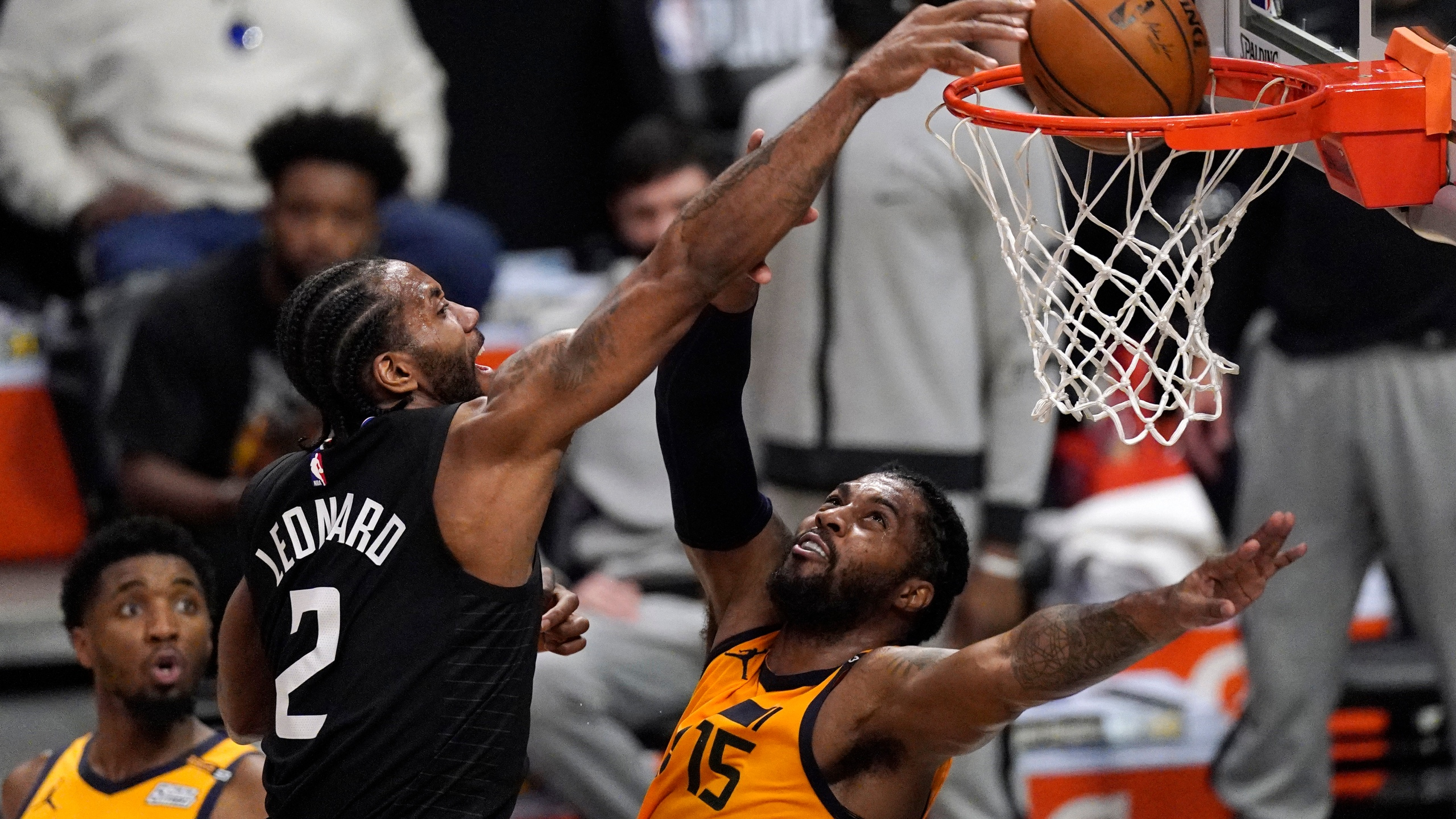Los Angeles Clippers forward Kawhi Leonard, center, dunks over Utah Jazz center Derrick Favors, right, as guard Donovan Mitchell watches during the first half in Game 4 of a second-round NBA basketball playoff series on June 14, 2021, in Los Angeles. (Mark J. Terrill / Associated Press)