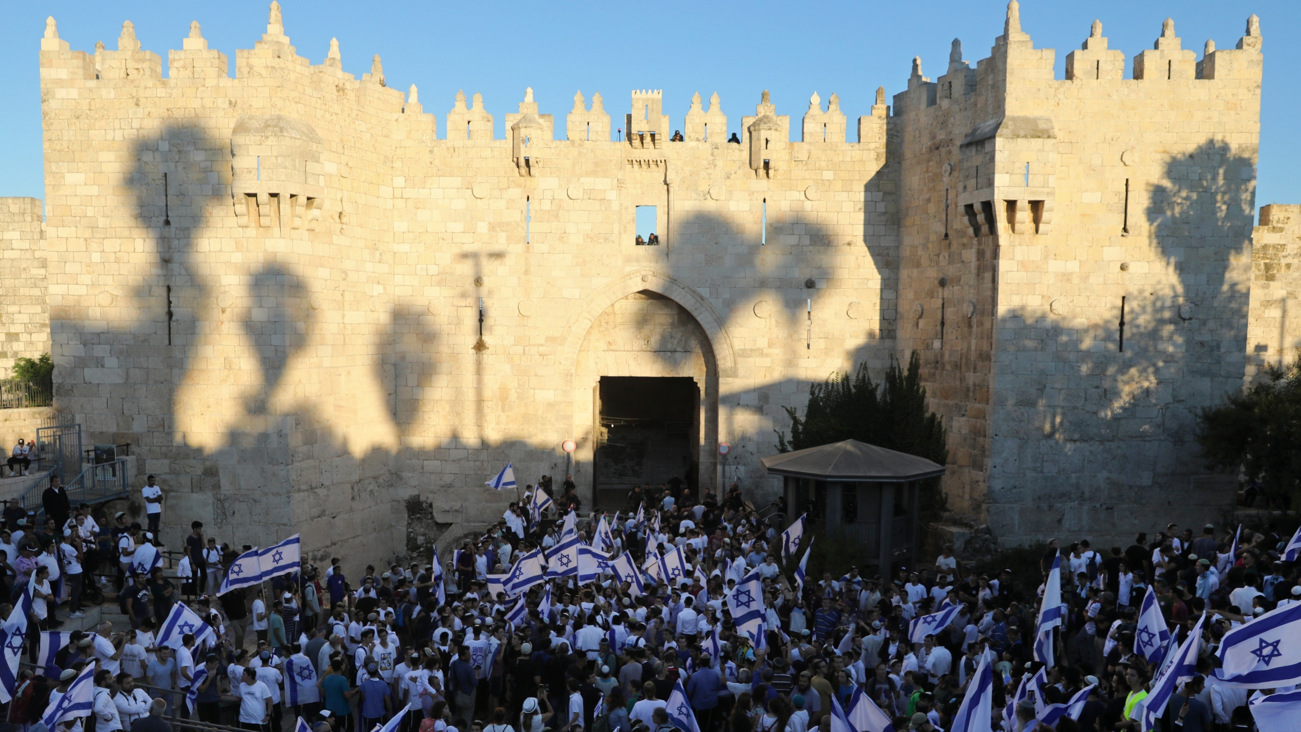 """Jewish ultranationalists wave Israeli flags during the """"Flags March,"""" next to Damascus gate, outside Jerusalem's Old City on June 15, 2021. (AP Photo/Mahmoud Illean)"""
