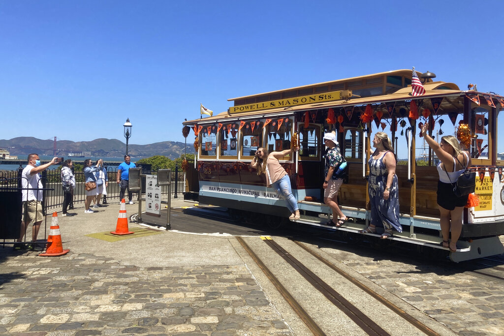 People pose for pictures on a cable car at the Hyde Street cable car turnaround in San Francisco on Tuesday, June 15, 2021. (AP Photo/Olga Rodriguez)