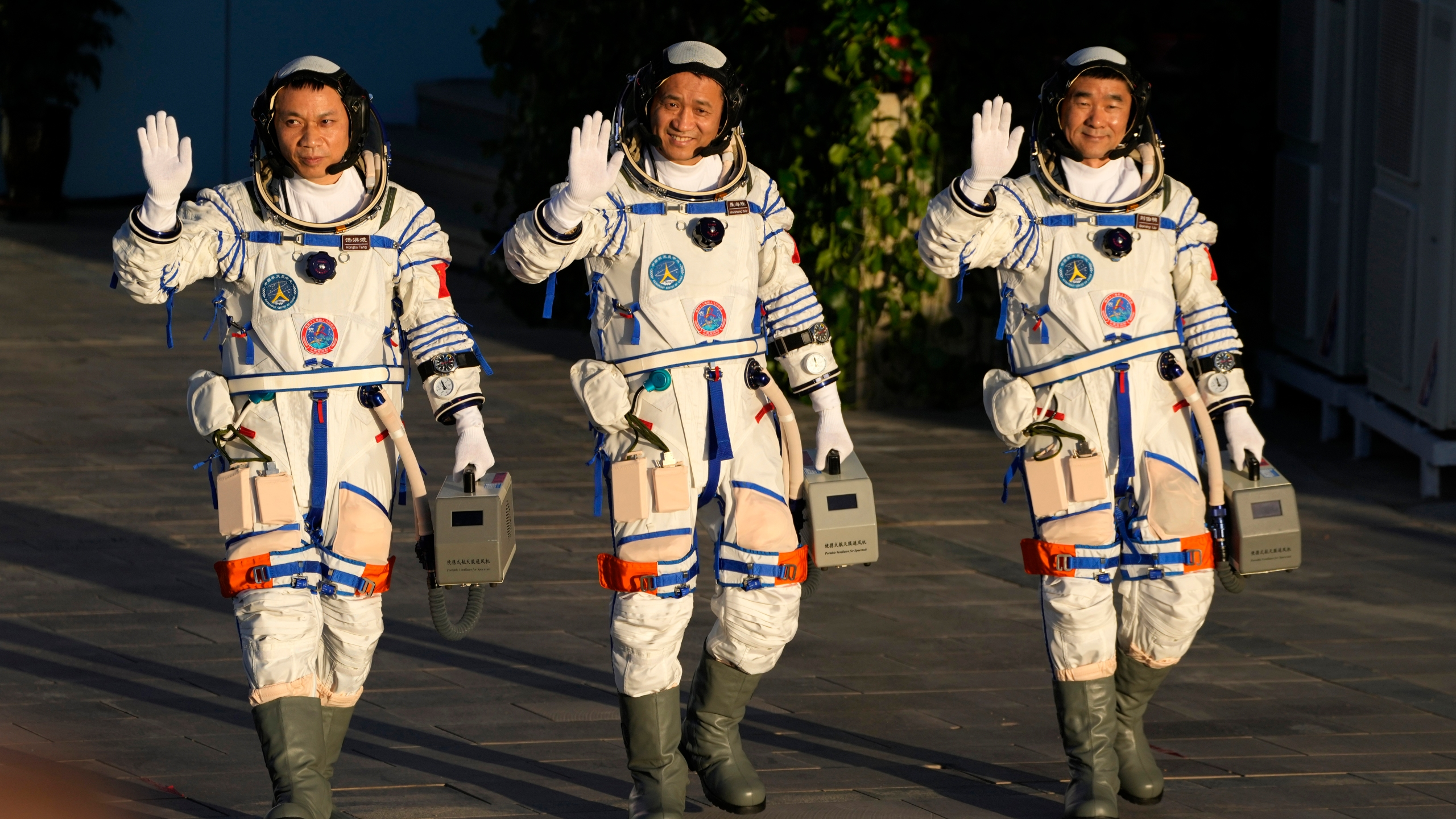 Chinese astronauts, from left, Tang Hongbo, Nie Haisheng, and Liu Boming wave as they prepare to board for liftoff at the Jiuquan Satellite Launch Center in Jiuquan in northwestern China on June 17, 2021. (AP Photo/Ng Han Guan)