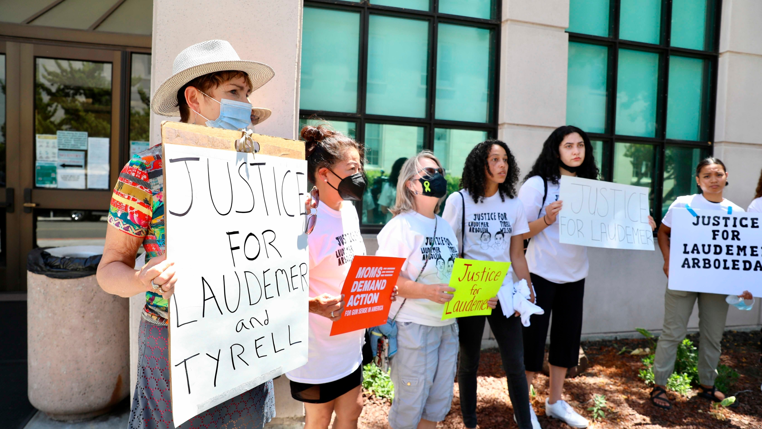 Supporters of the late Laudemer Arboleda and the late Tyrell Wilson hold signs following an arraignment hearing for Danville police officer Andrew Hall outside the A.F. Bray Courthouse in Martinez, Calif., on June 16, 2021.(Yalonda M. James/San Francisco Chronicle via AP)