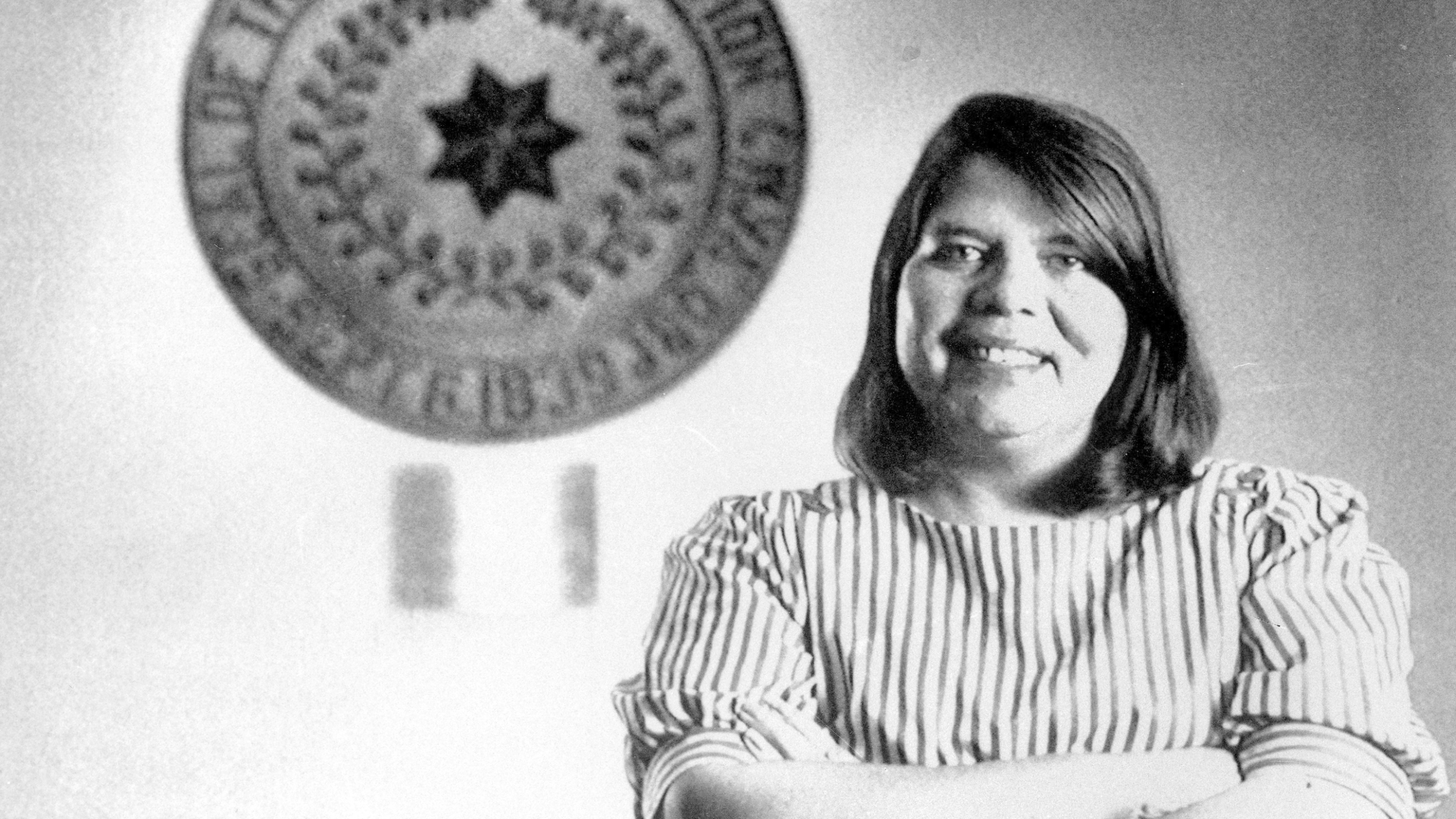In this July 19, 1985, file photo, Wilma Mankiller, the first woman elected chief of the Cherokee Nation, poses in front of the tribal emblem at the Cherokee Nation in Oklahoma. The U.S. Mint says Mankiller will be among the first five women honored in the new American Women Quarters Program, which starts in 2022 and continues until 2025. (AP Photo, File)