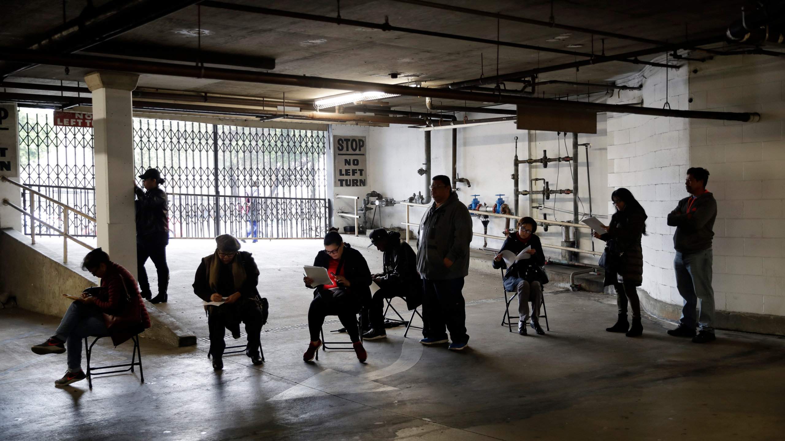 Unionized hospitality workers wait in line in a basement garage to apply for unemployment benefits at the Hospitality Training Academy in Los Angeles on March 13, 2020. (Marcio Jose Sanchez / Associated Press)
