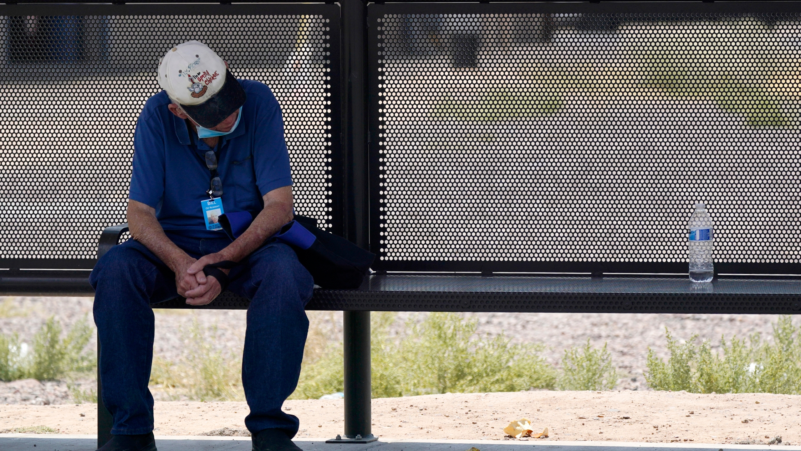 A person waits for a bus in the shade as the heat wave in the Western states continues on June 17, 2021, in Phoenix. (AP Photo/Ross D. Franklin)