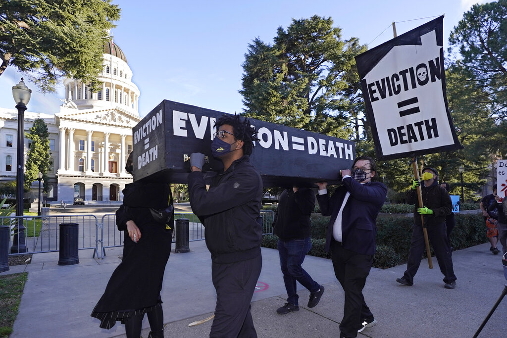In this Jan. 25, 2021, file photo, demonstrators call passage of rent forgiveness and stronger eviction protections legislation and carry a mock casket past the Capitol in Sacramento, Calif. (AP Photo/Rich Pedroncelli, File)