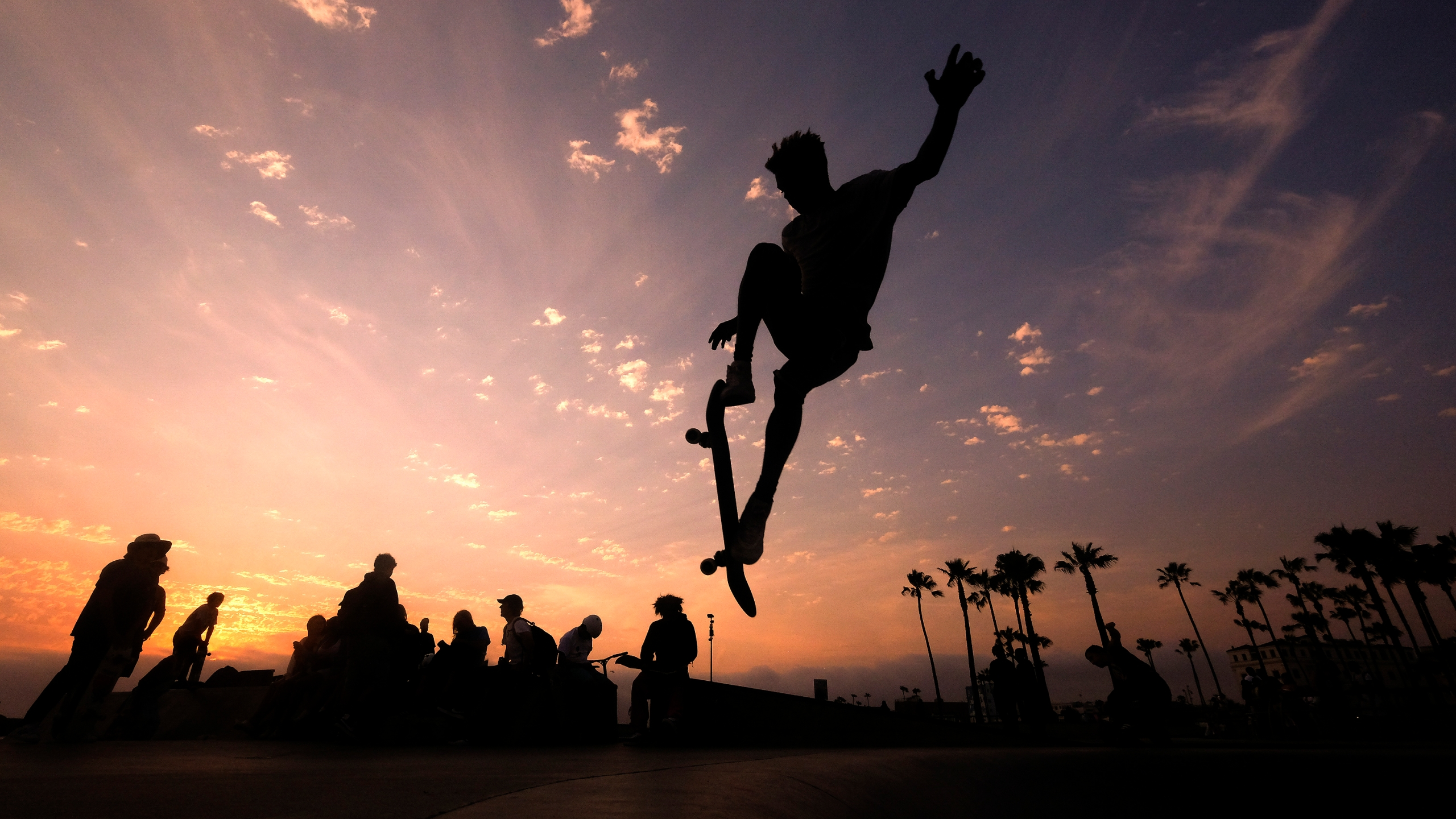 In this Wednesday, June 16, 2021, file photo, a skateboarder is silhouetted as he jumps high at the skateboard park during sunset in the Venice Beach section of Los Angeles. The Southwest U.S. continued to bake Saturday, June 19, and weather forecasters kept warnings in effect for excessive heat in Arizona, Nevada and desert areas, at least through the weekend. (AP Photo/Ringo H.W. Chiu, File)