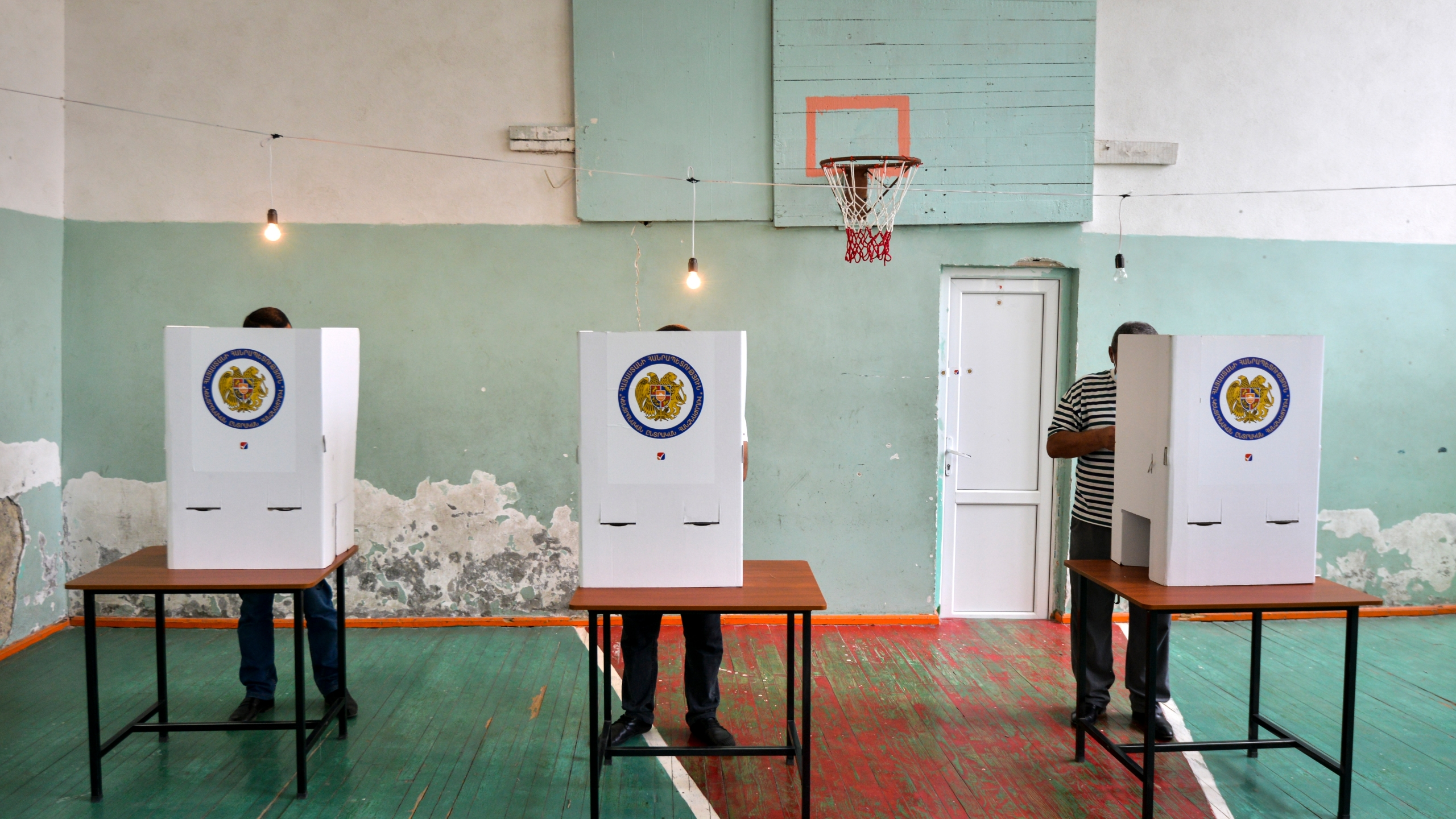 Voters read their ballots at a polling station in a school's sport hall during a parliamentary elections in Yerevan, Armenia, Sunday, June 20, 2021. (Karo Sahakyan/PAN Photo via AP)