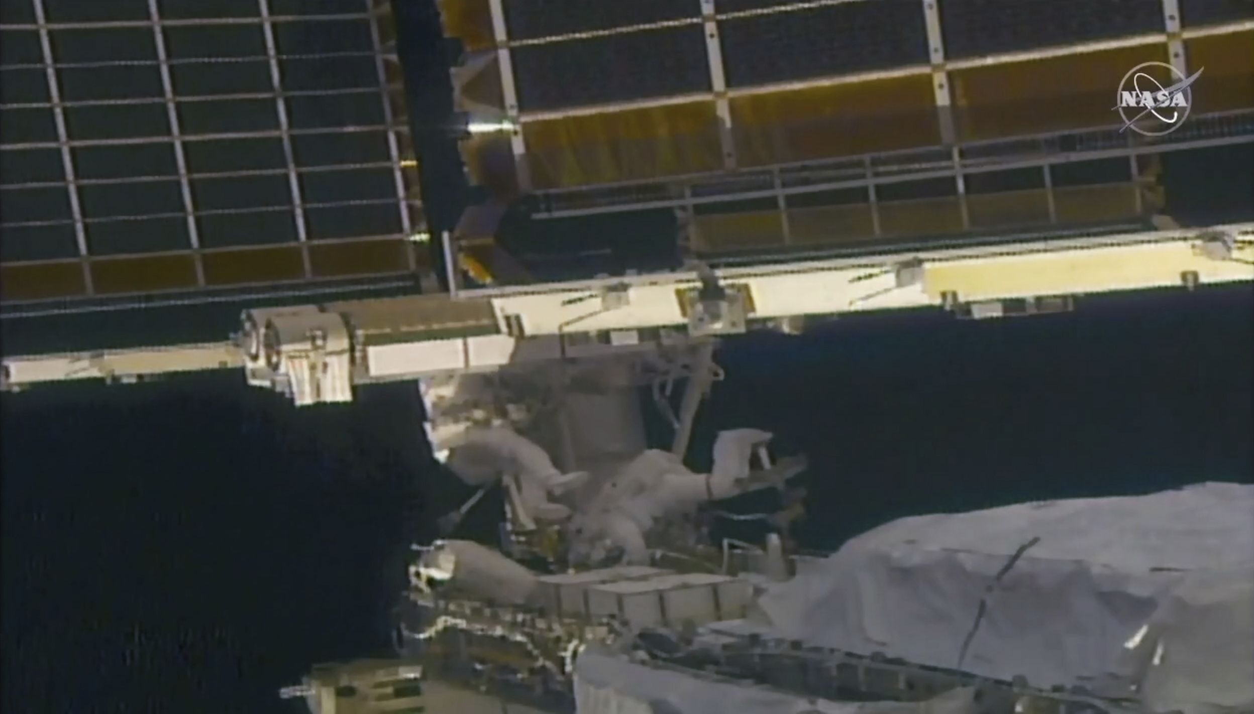 In this image taken from NASA video, NASA astronaut Shane Kimbrough, left, and French astronaut Thomas Pesquet work on the solar array outside the International Space Station, Sunday, June 20 2021. (NASA via AP)