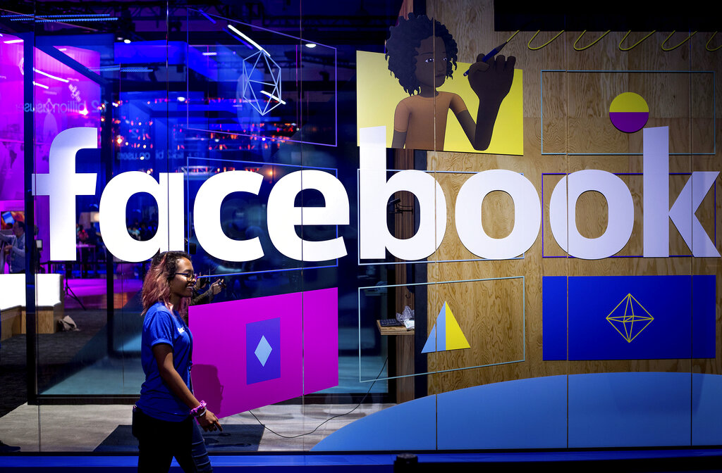 In this April 18, 2017, file photo, a conference worker passes a demo booth at Facebook's annual F8 developer conference, in San Jose, Calif. (AP Photo/Noah Berger, File)