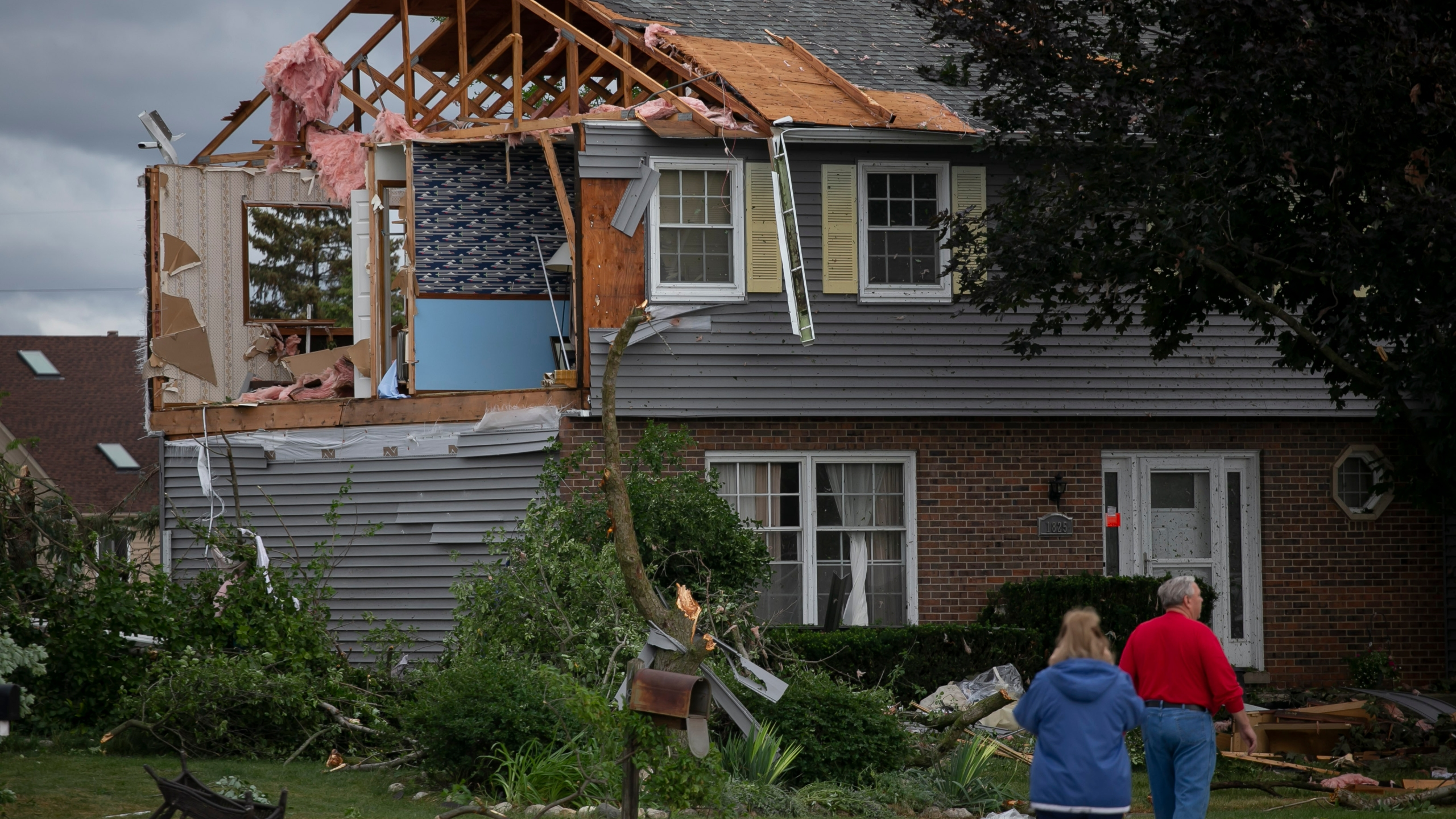 People walk near a damaged home on Princeton Circle in Naperville's Ranchview neighborhood after a tornado swept through the area, Monday, June 21, 2021, in Ill. (Rich Hein/Chicago Sun-Times via AP)