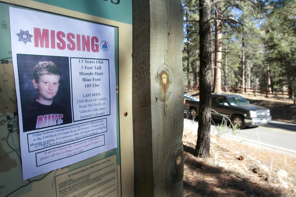In this Nov. 26, 2012, file photo, a missing poster of 13-year-old Dylan Redwine hangs on a trail head sign next to Vallecito Reservoir in Vallecito, Colorado.(Shaun Stanley/The Durango Herald via AP, File)
