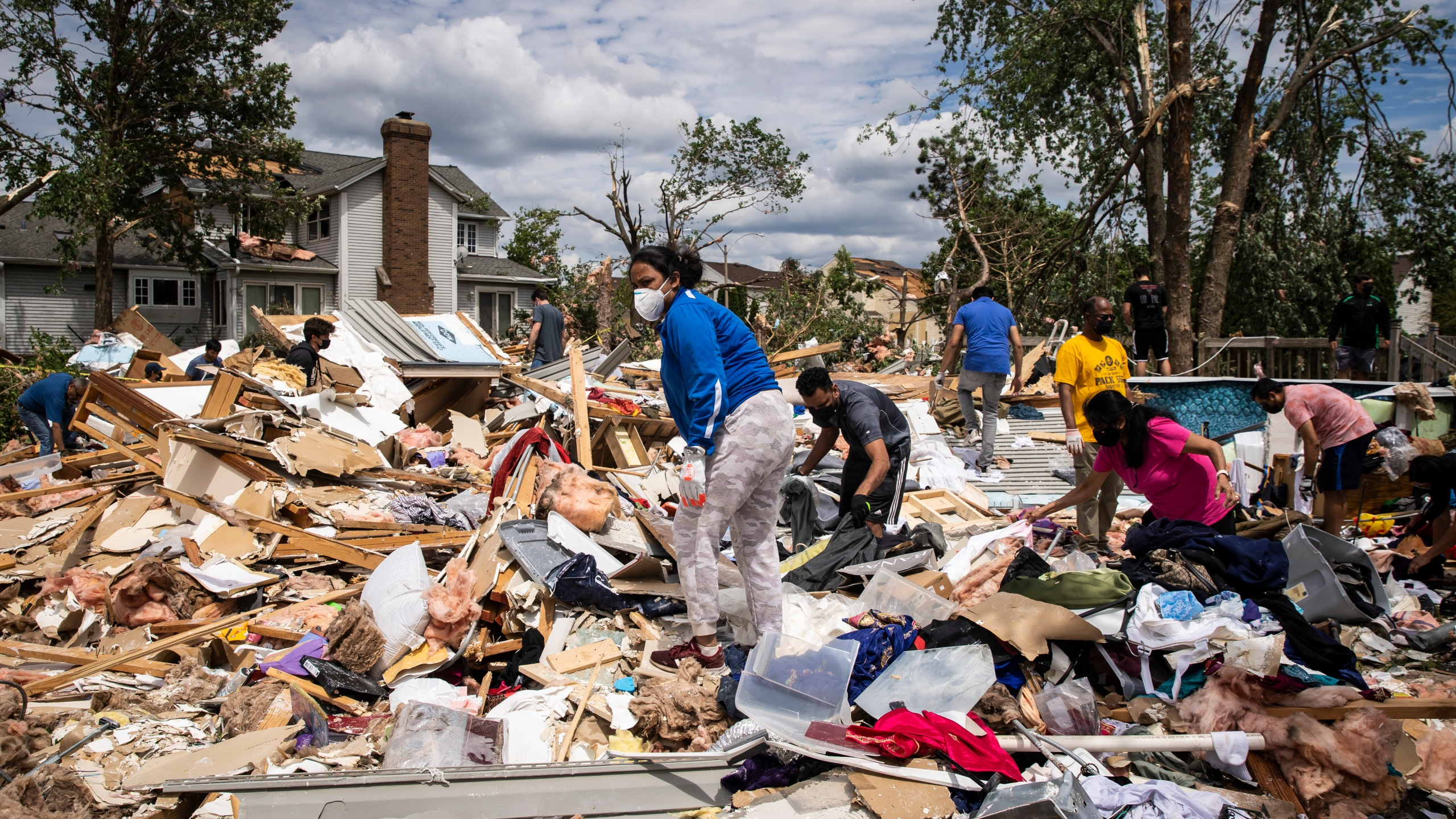 Dozens of volunteers help clean up a demolished home on Princeton Circle near Ranchview Drive in Naperville after a tornado ripped through the western suburbs overnight, Monday afternoon, June 21, 2021. (Ashlee Rezin Garcia/Sun-Times/Chicago Sun-Times via AP)