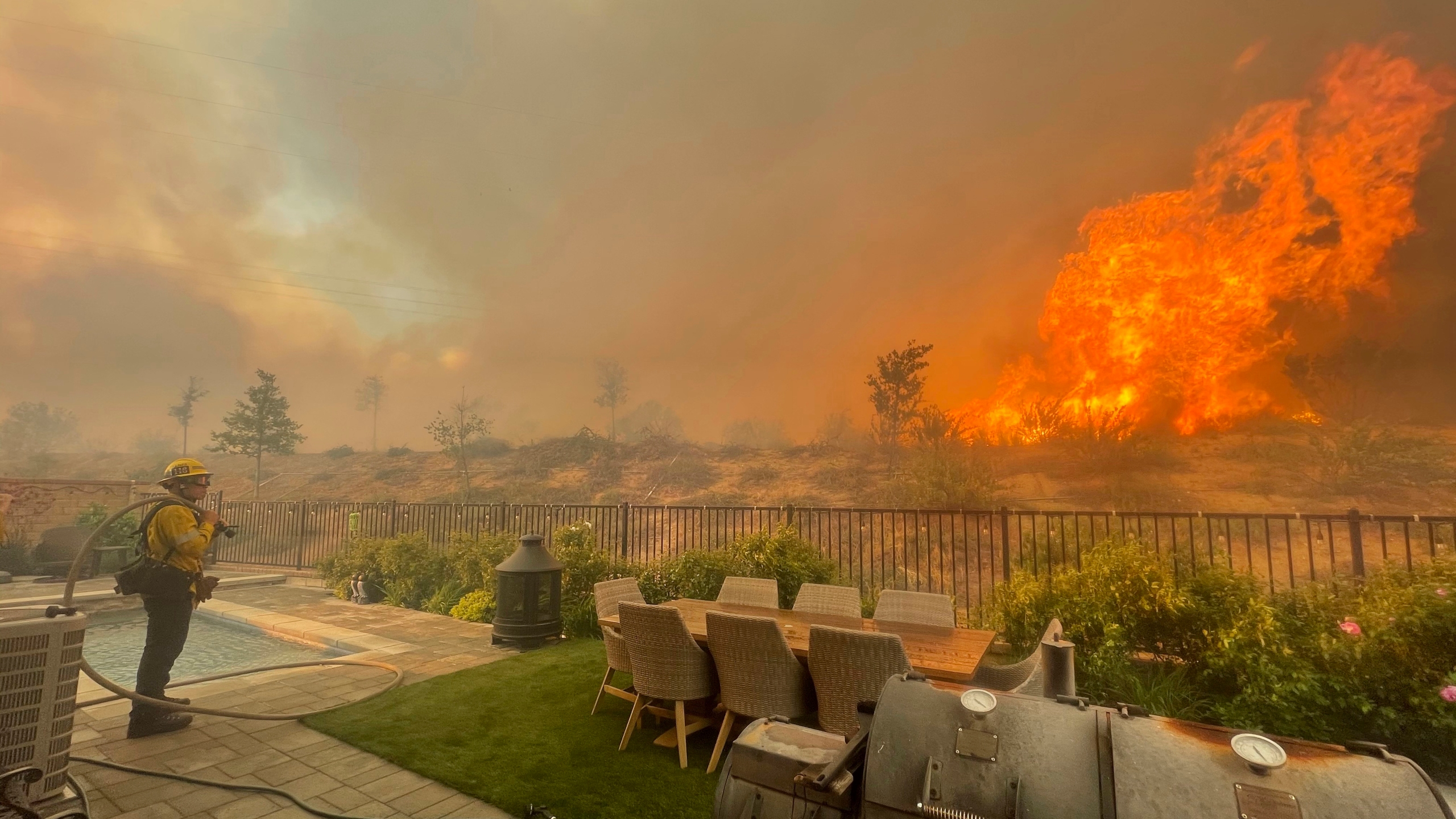 In this April 28, 2021, file photo, a firefighter prepares to battle the North Fire from a backyard on Via Patina, in Santa Clarita. (Emily Alvarenga//The Santa Clarita Valley Signal via AP, File)