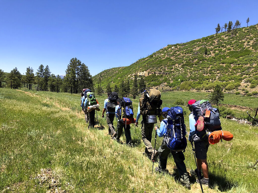 In this June 10, 2021 photo provided by Barry Bedlan, members of Troop 298 of Frisco, Texas are among the first to embark a 12-day trek across the Philmont Scout Ranch, outside Cimarron, N.M. (Barry Bedlan via AP)